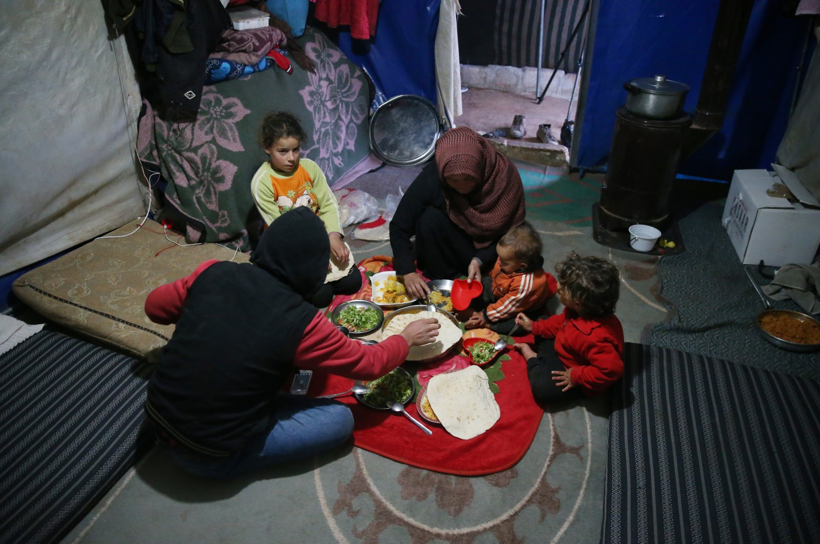 A Syrian refugee family has their iftar meal in a camp in Idlib, Syria, April 13, 2021. (AA)