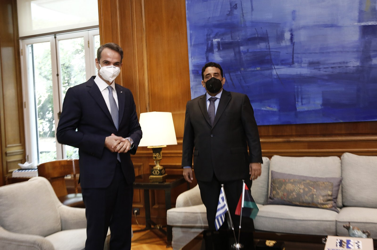 Greek Prime Minister Kyriakos Mitsotakis (L) stands next to the head of Libya's Presidential Council, Mohammad Younes Menfi, during their meeting in Athens, Greece, 14 April 2021. (EPA Photo)