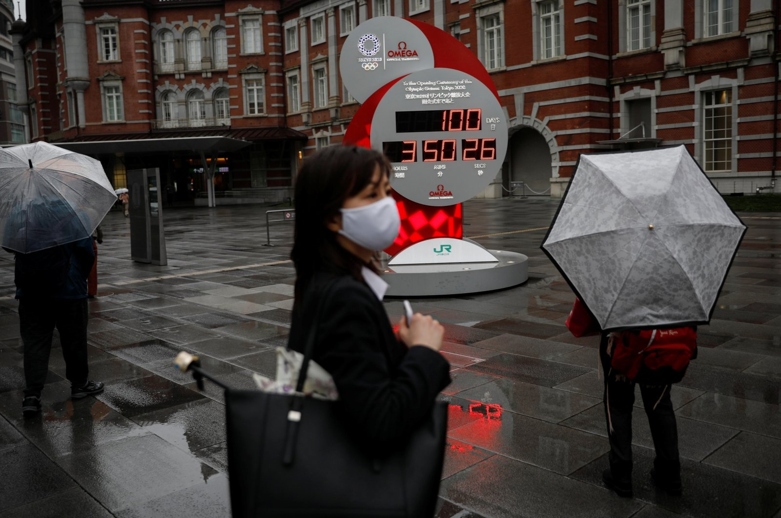 A woman wearing a protective face mask walks in front of a countdown clock showing that 100 days are left until the Tokyo 2020 Olympic Games that have been postponed to 2021 due to the COVID-19 pandemic, Tokyo, Japan, April 14, 2021. (Reuters Photo)