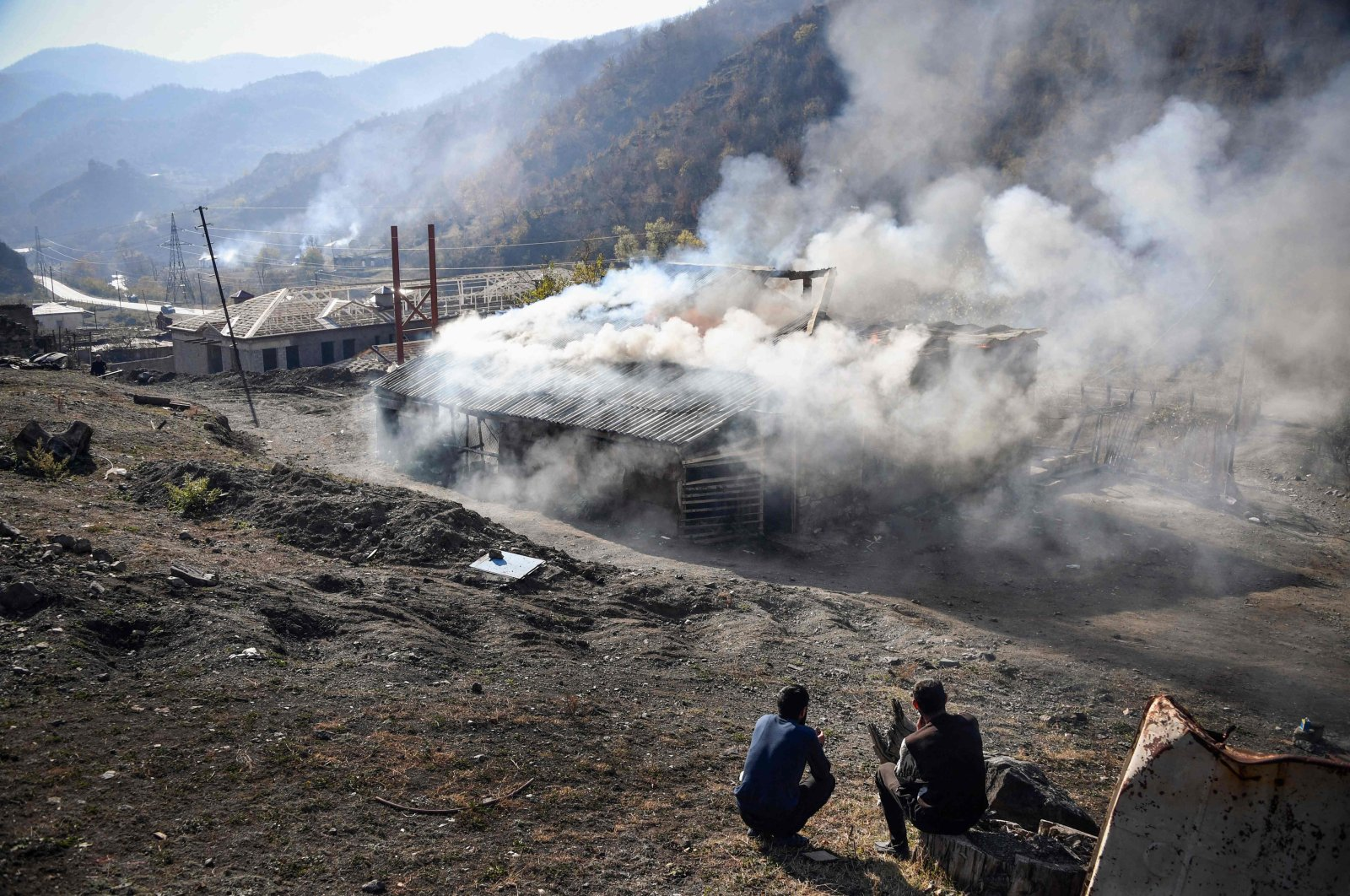 Residents look at burning houses in the village of Charektar outside the town of Kalbajar, during the military conflict between Armenia and Azerbaijan over the breakaway region of Nagorno-Karabakh, Nov. 14, 2020. (AFP)