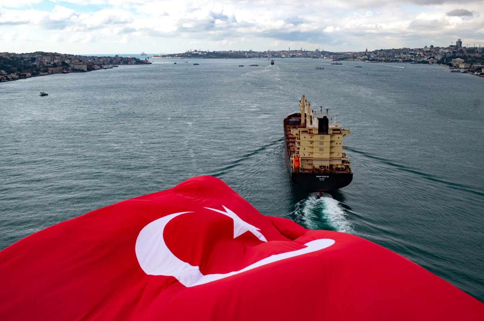 The Turkish national flag waves on the July 15 Martyrs' Bridge, formerly known as the Bosporus Bridge, as a ship sails through the Bosporus, in Istanbul, Turkey Nov. 8, 2020. (AFP Photo)