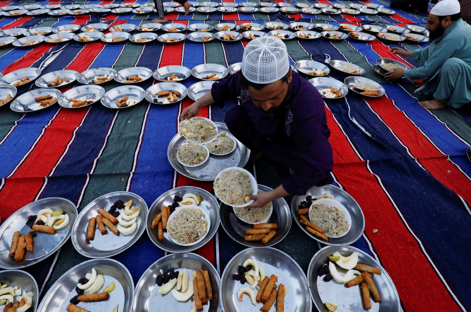 A man arranges plates of food for iftar during the fasting month of Ramadan, as the COVID-19 outbreak continues, at a mosque in Karachi, Pakistan, April 14, 2021. (Reuters Photo)