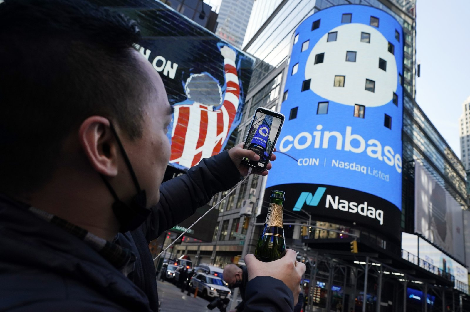 Coinbase employee Daniel Huynh holds a celebratory bottle of champagne as he takes a photograph outside the Nasdaq MarketSite, in Times Square, New York, U.S., Wednesday, April 14, 2021. (AP Photo)