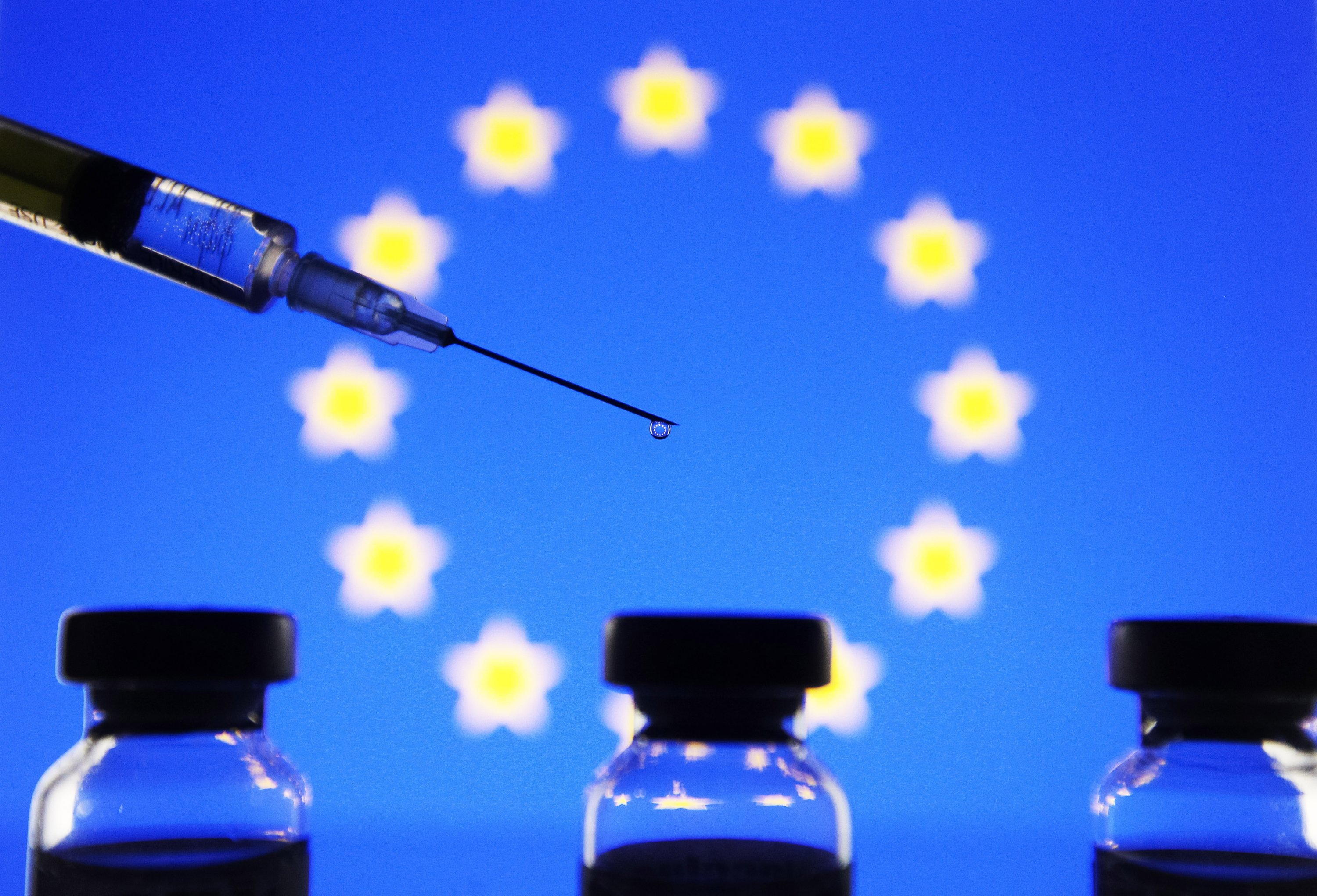 In this photo illustration, vials and a medical syringe are seen in front of the EU flag, Ukraine, Dec. 19, 2020. (Photo by Getty Images)