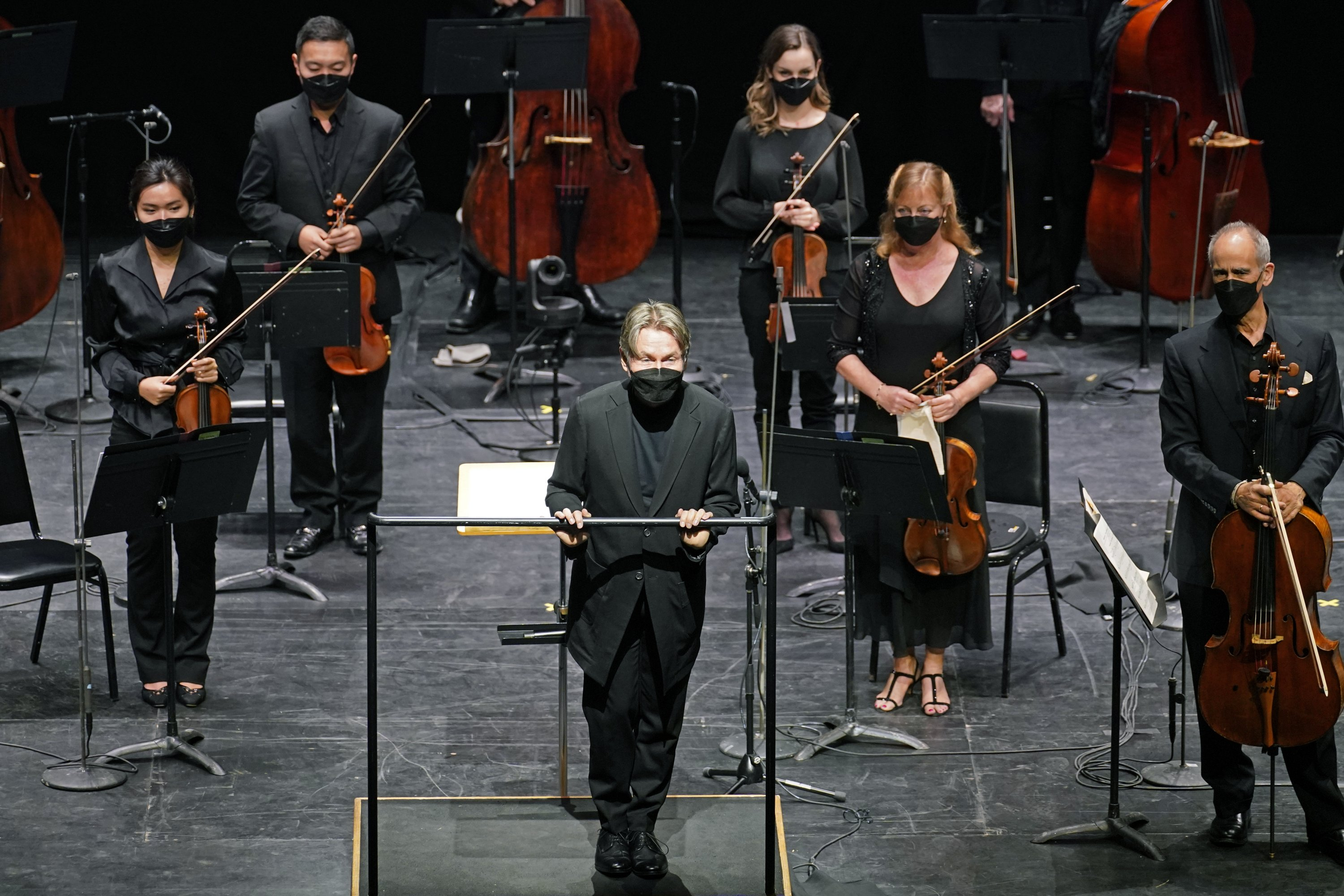 Guest conductor Essa Pekka Salonen (C) greets a live audience as New York Philharmonic musicians stand behind him before they performed together for the first time since March 10, 2020, at The Shed in Hudson Yards, New York, U.S., Wednesday, April 14, 2021. (AP Photo)