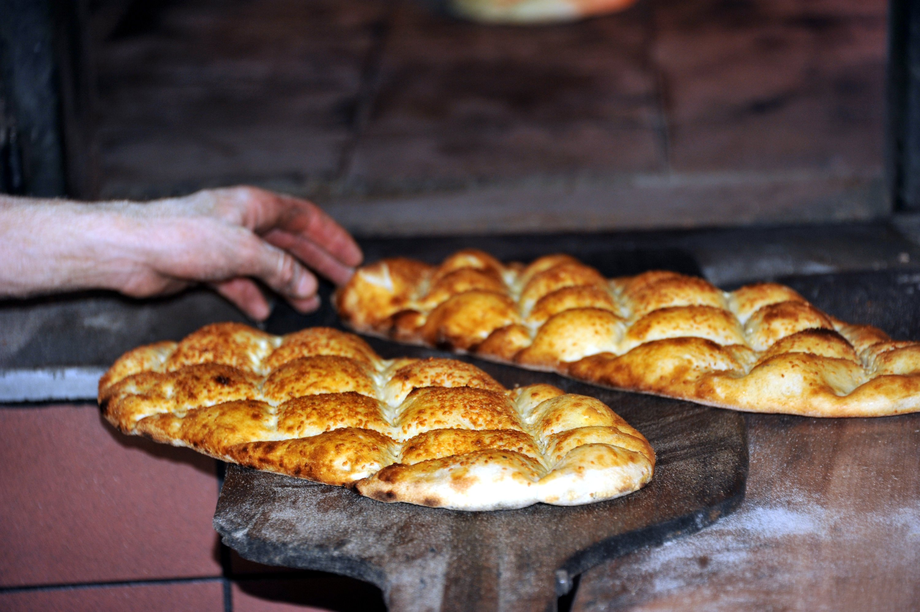 A bread baker takes two special round baked flatbreadsreferred to as the Ramazan pide, made from an oven-baked enriched dough and sprinkled with nigella and sesame seeds on top,out of the oven,Tokat, Turkey, April 13, 2021. (AA Photo)