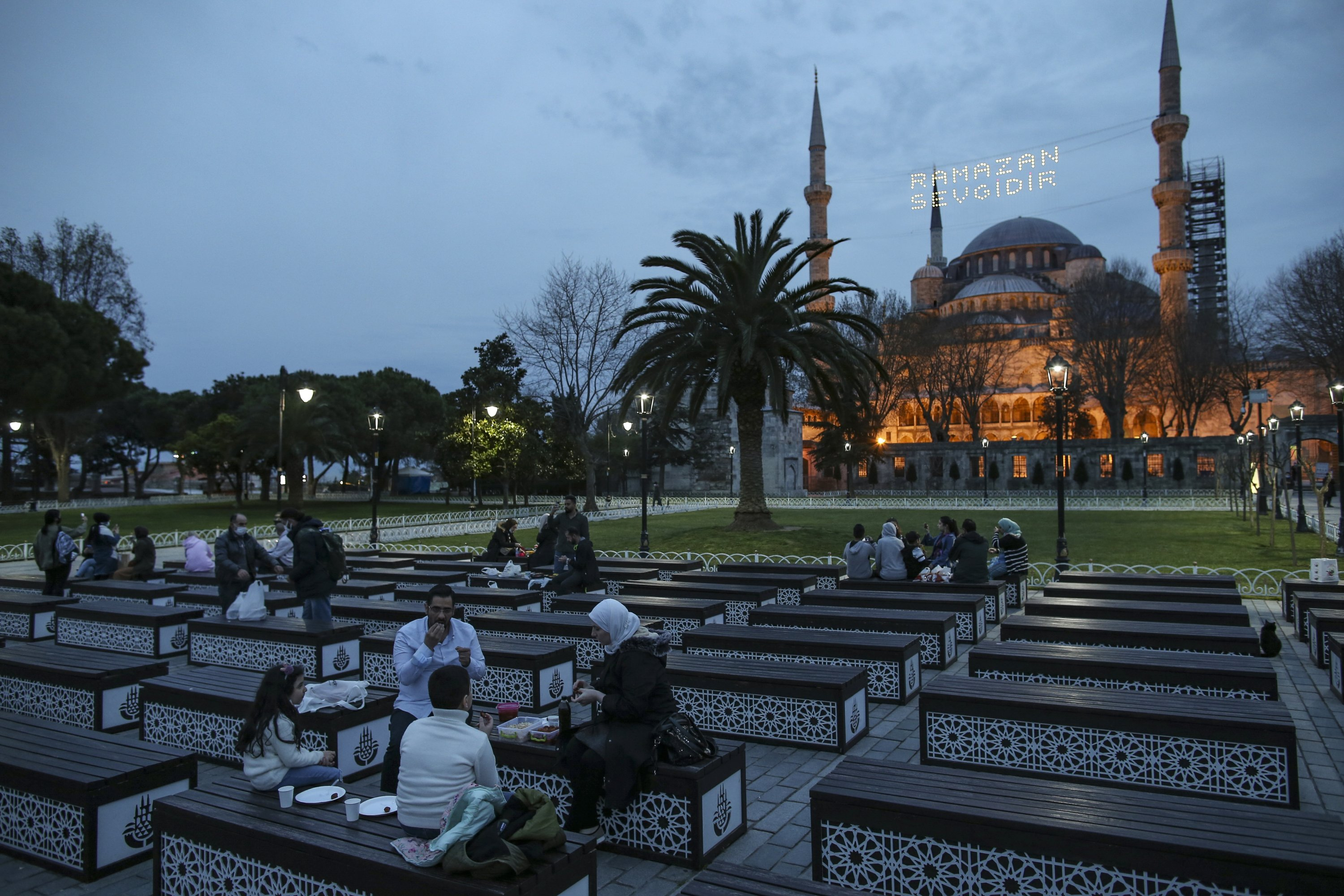 """People break their fast in front of the iconic Sultan Ahmed Mosque, or the Blue Mosque, decorated with lights reading """"Ramadan is love,"""" marking the holy month of Ramadan, in Istanbul, Turkey, April 13, 2021. (AP Photo)"""