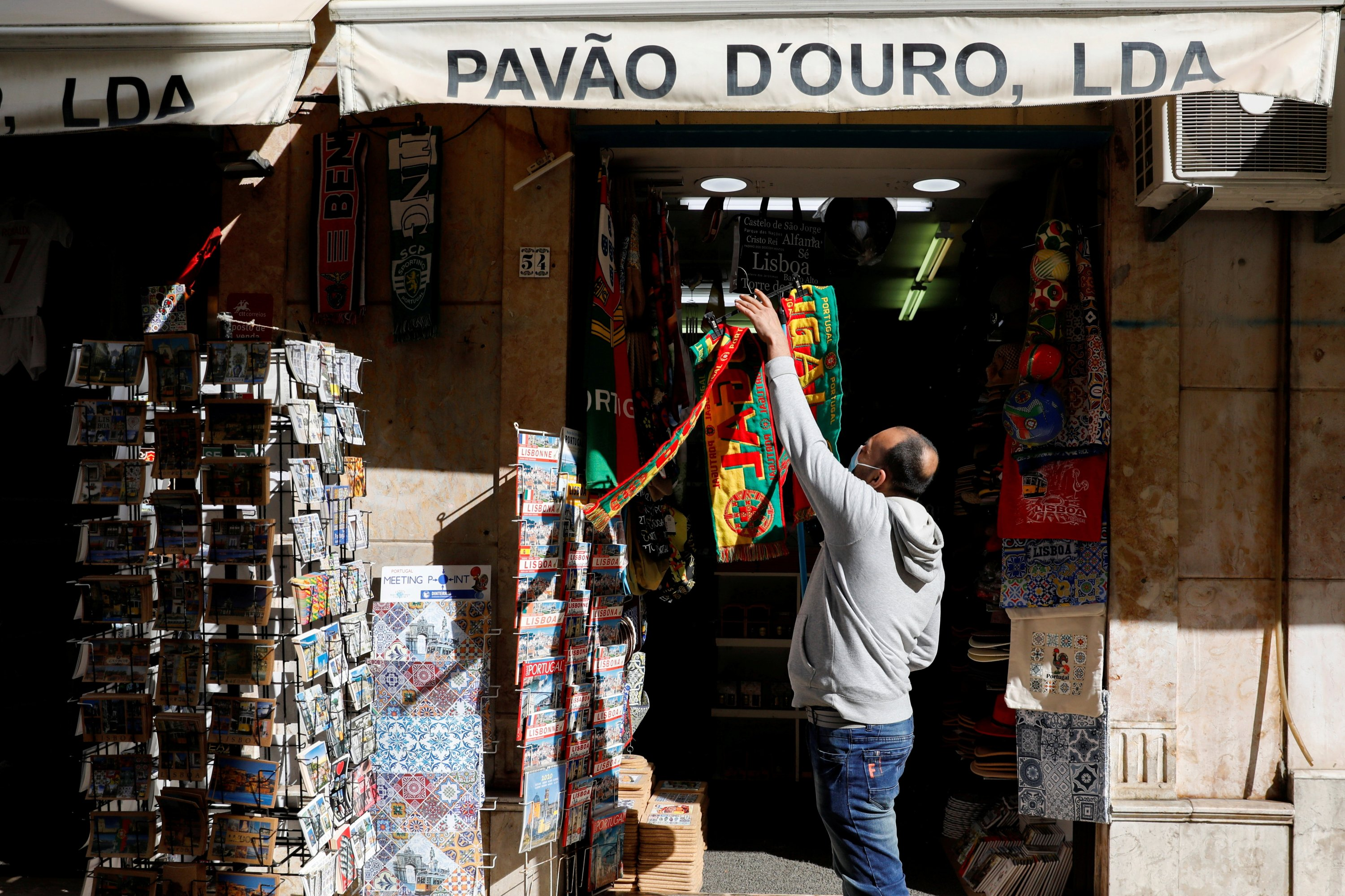 A man hangs football scarves in a store on the first day of the reopening after a country lockdown, amid the coronavirus disease (COVID-19) pandemic, in Lisbon, Portugal, April 5, 2021. (REUTERS/File Photo)