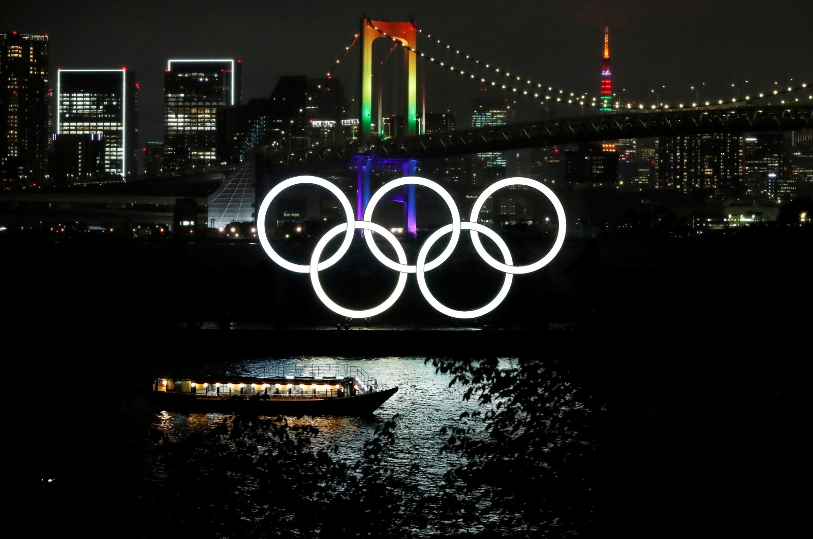 The Rainbow Bridge and Tokyo Tower are illuminated with Olympic colors to mark 100 days countdown to the Tokyo 2020 Olympics that have been postponed to 2021 due to the coronavirus disease (COVID-19) outbreak, in Tokyo, Japan April 14, 2021. (Reuters Photo)