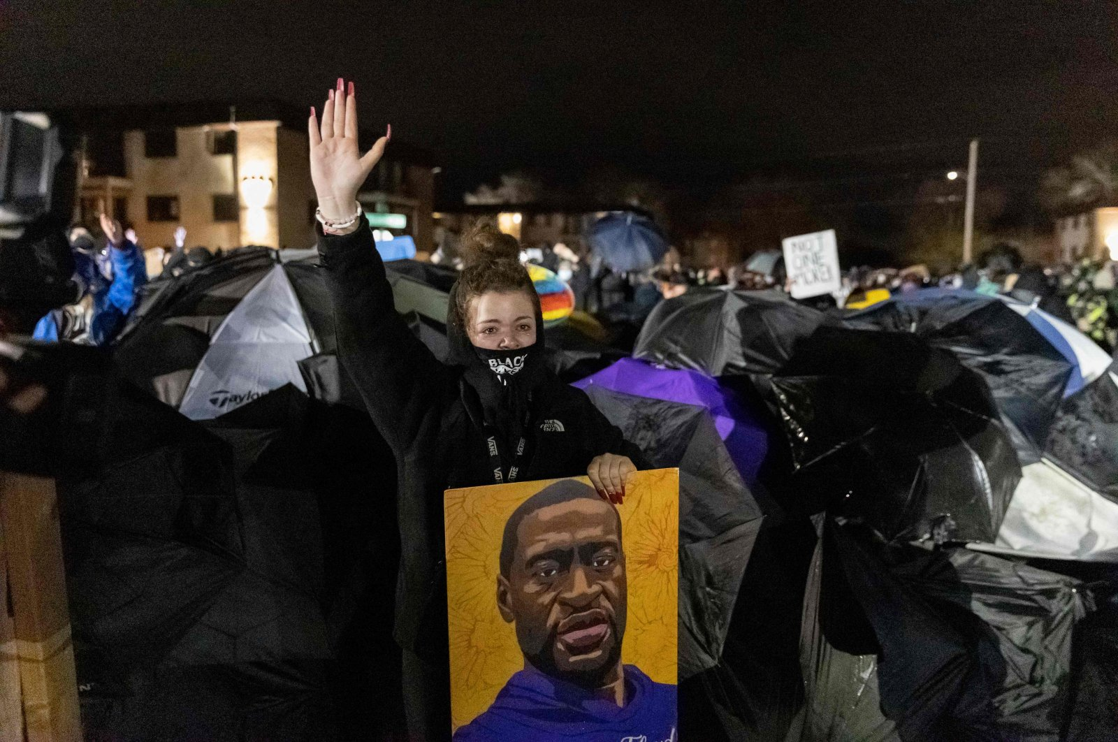 A demonstrator holding a poster of George Floyd, raises her hand toward a line of police officers outside the Brooklyn Center police station while protesting the death of Daunte Wright who was shot and killed by a police officer in Brooklyn Center, Minnesota, April 14, 2021. (AFP Photo)