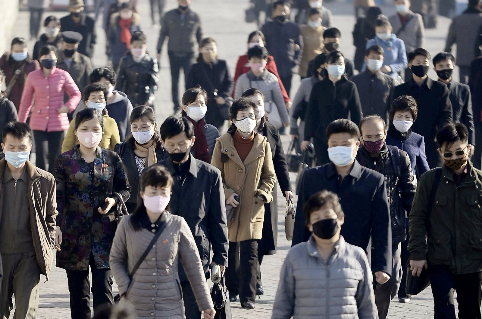 People wearing protective face masks commute amid concerns over COVID-19 in Pyongyang, North Korea, March 30, 2020. (Kyodo via Reuters)