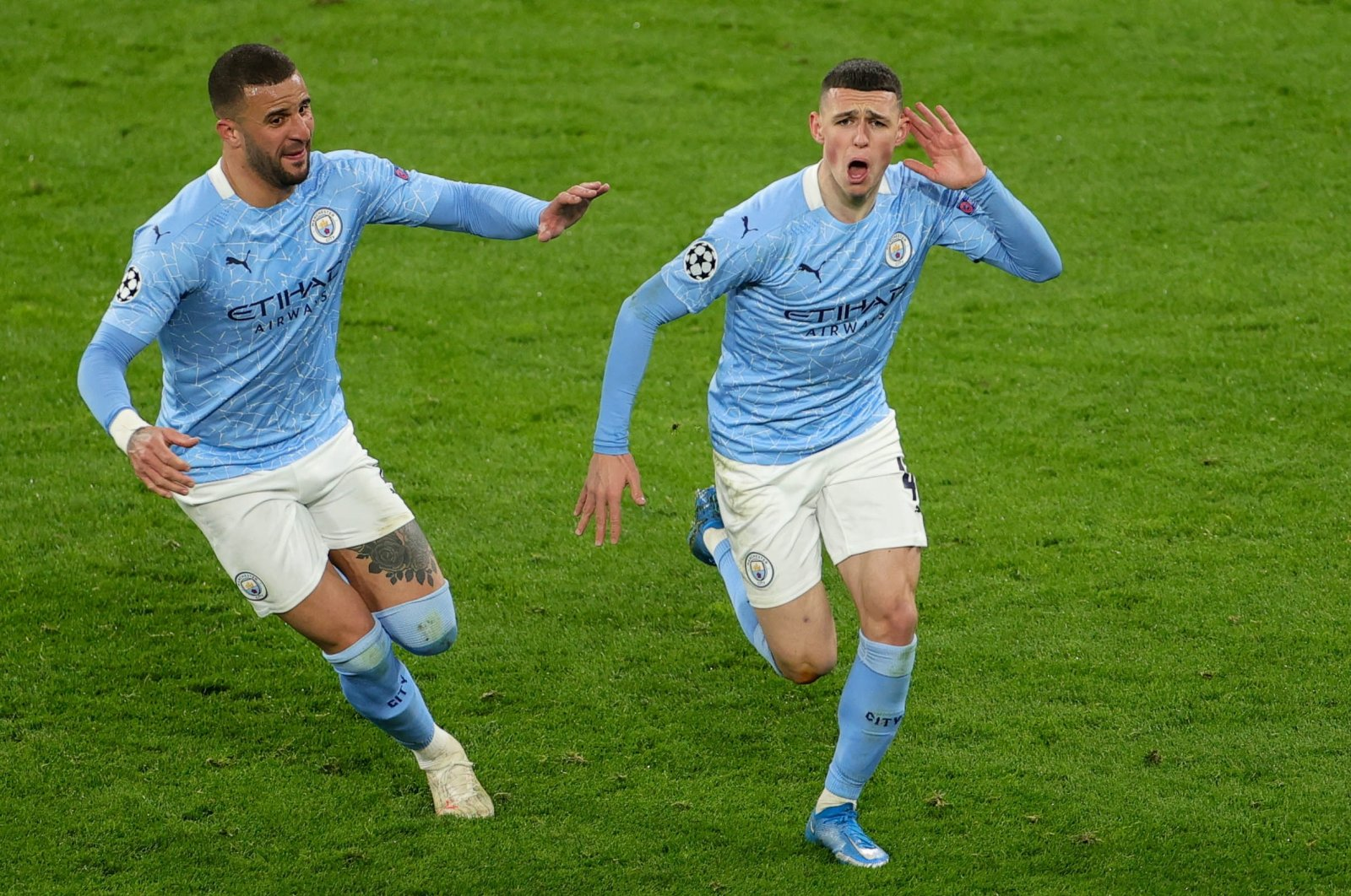 Manchester City's Phil Foden (R) celebrates with teammate Kyle Walker after scoring against Borussia Dortmund in the UEFA Champions League quarterfinal, second leg match in Dortmund, Germany, April 14, 2021. (EPA Photo)