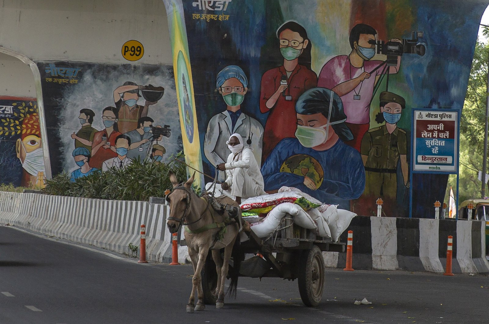 A man rides a horse cart past a mural depicting frontline workers in Noida, a suburb of New Delhi, India, Thursday, April 15, 2021. (AP Photo)