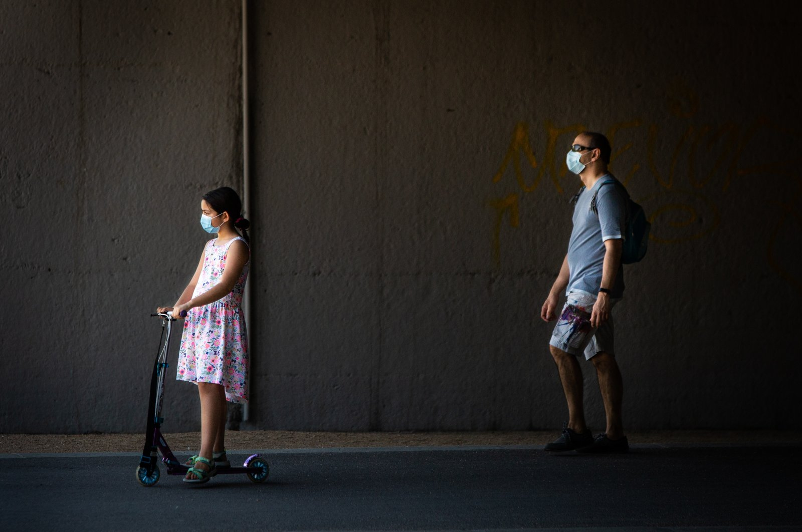 A little girl wearing a protective face mask rides an electric scooter as her father walks behind her through Madrid Rio Park amid the coronavirus outbreak, Madrid, Spain, May 25, 2020. (Photo by Getty Images)
