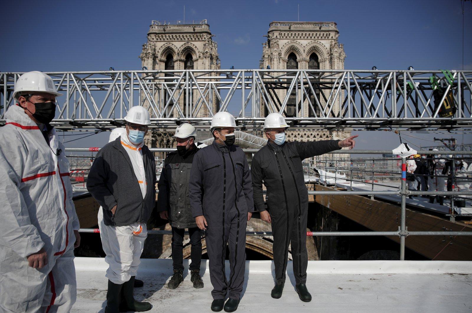 French President Emmanuel Macron (C) visits the reconstruction site of the Notre Dame cathedral, Paris, France, April 15, 2021. (Pool via AP)