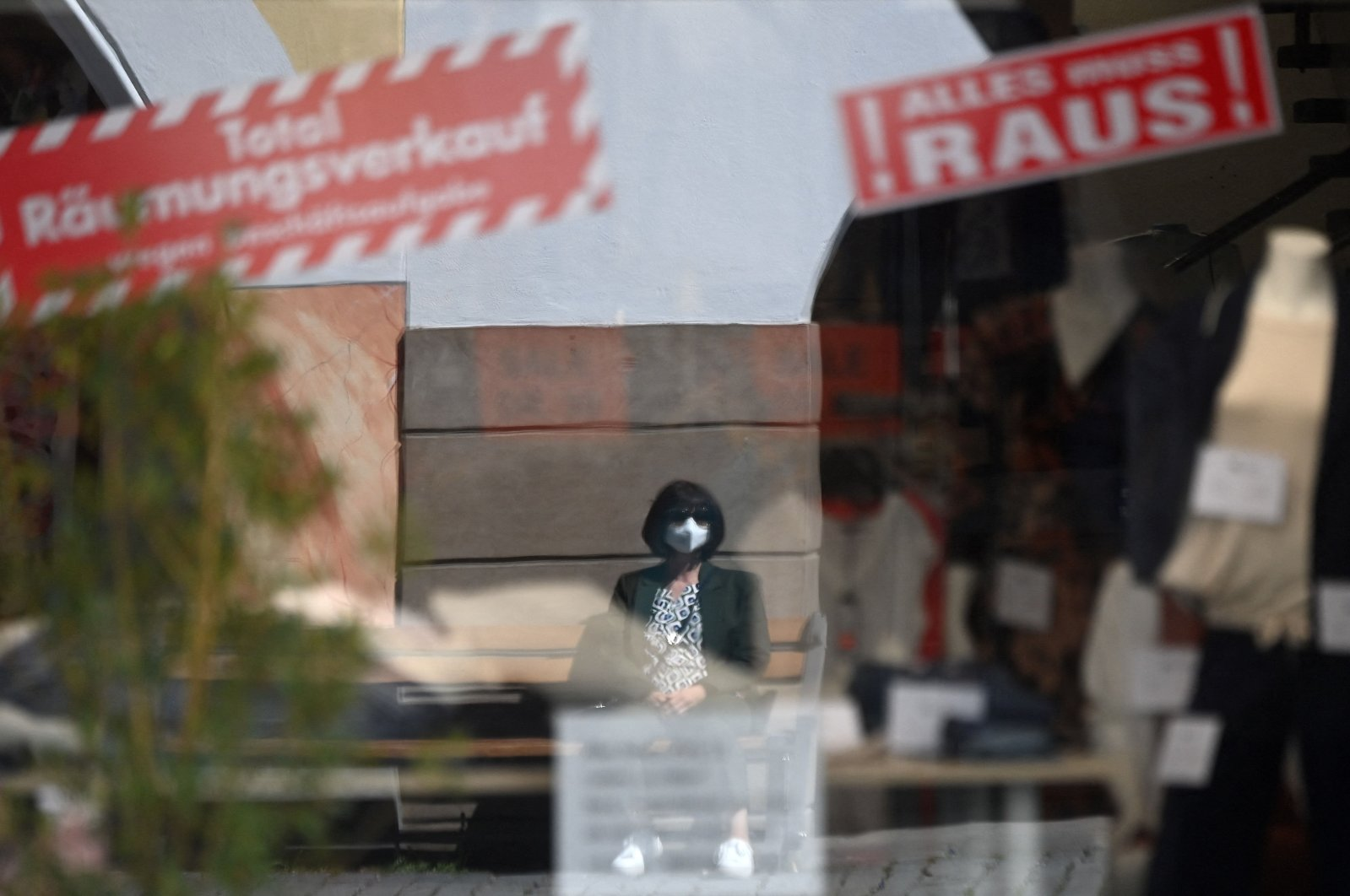 A woman wearing a protective face mask is reflected in the window of a store advertising a closing-down sale in the Bavarian city of Rosenheim, southern Germany, April 1, 2021. (AFP Photo)