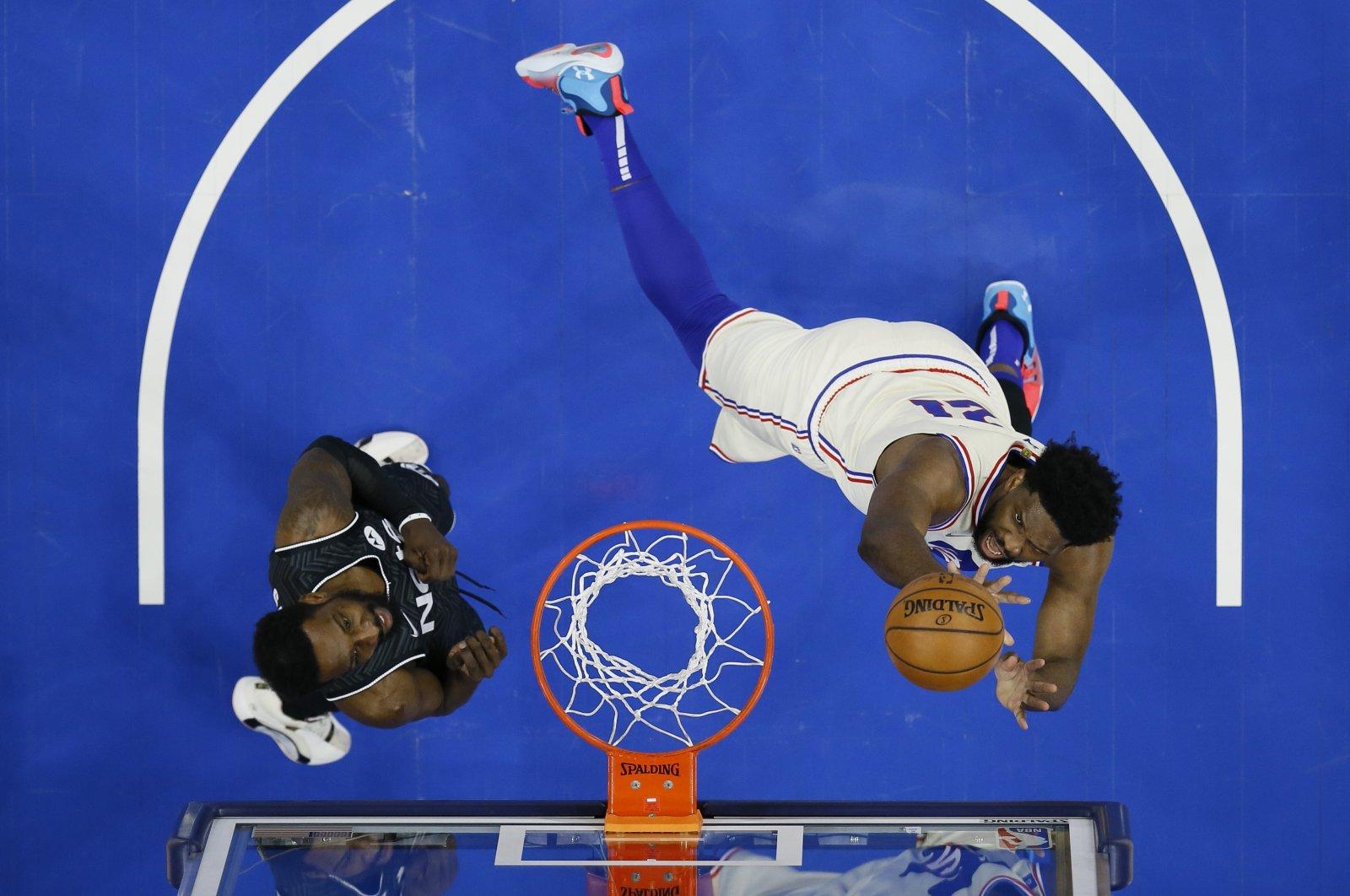 Philadelphia 76ers' Joel Embiid (R) goes up for a shot against Brooklyn Nets' Jeff Green during an NBA game, Philadelphia, U.S. April 14, 2021. (AP Photo)