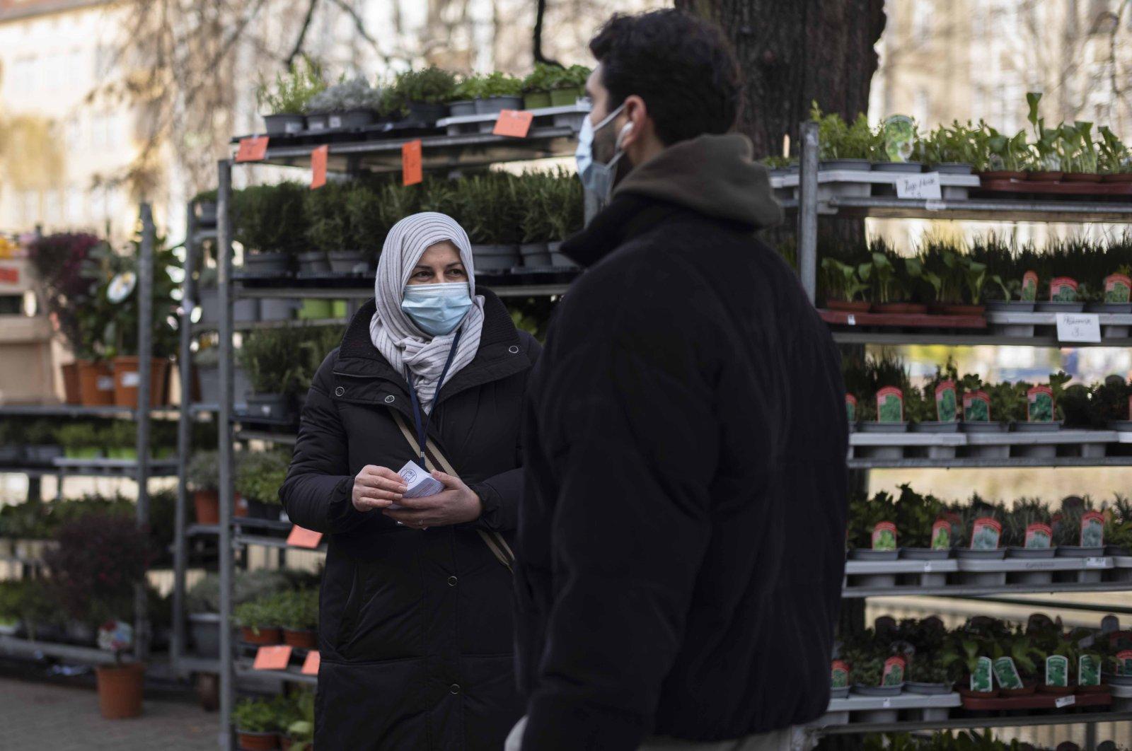 Aliye Türkyılmaz (L), a member of a multilingual team of five street vendors, stands in a market in Berlin, Germany, March 9, 2021. (AP Photo)