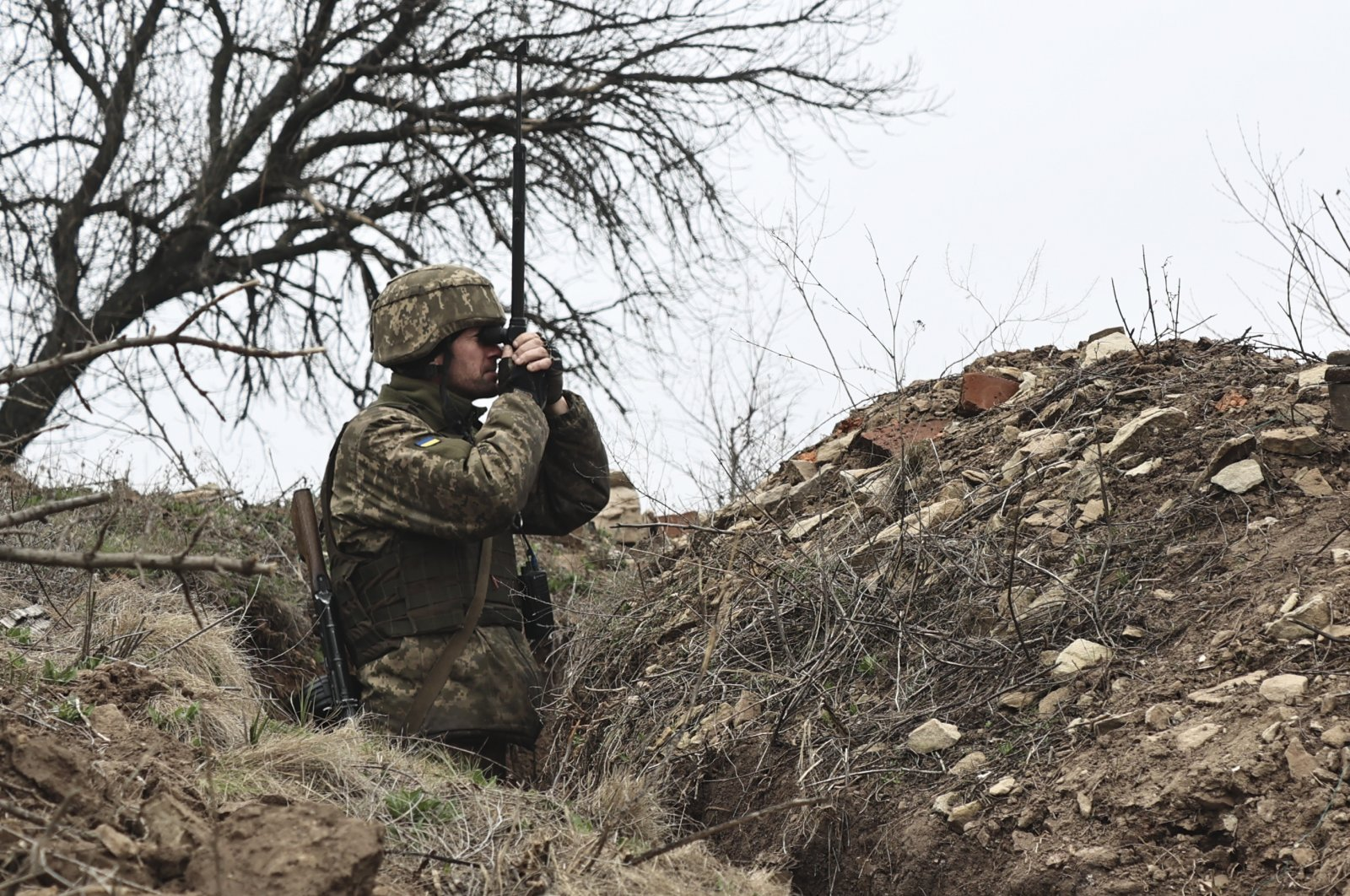 A Ukrainian soldier watches fighting positions through a periscope on the line of separation from pro-Russian rebels near Donetsk, Ukraine, April 12, 2021. (AP Photo)