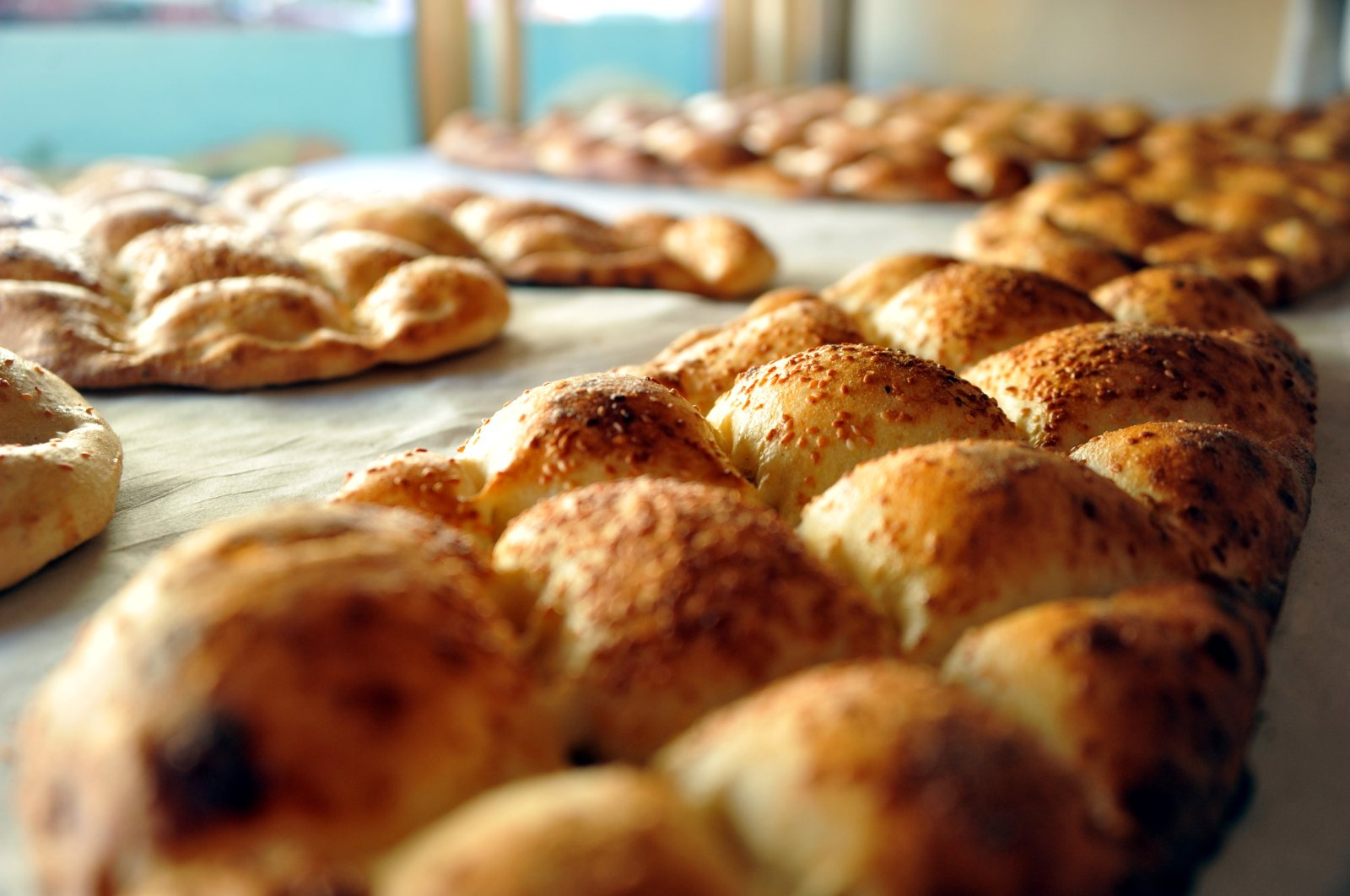 Several special round baked flatbreadreferred to as the Ramazan pide, made from an oven-baked enriched dough and sprinkled with nigella and sesame seeds on top,siton a counter inTokat, Turkey, April 13, 2021. (AA Photo)