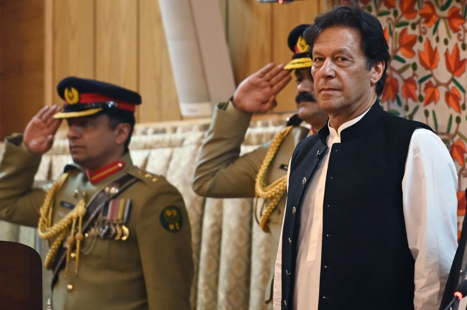Pakistan's Prime Minister Imran Khan (R) listens to the national anthem as he arrives at the legislative assembly in Muzaffarabad, the capital of Pakistan-controlled Kashmir, Aug. 14, 2019. (AFP Photo)