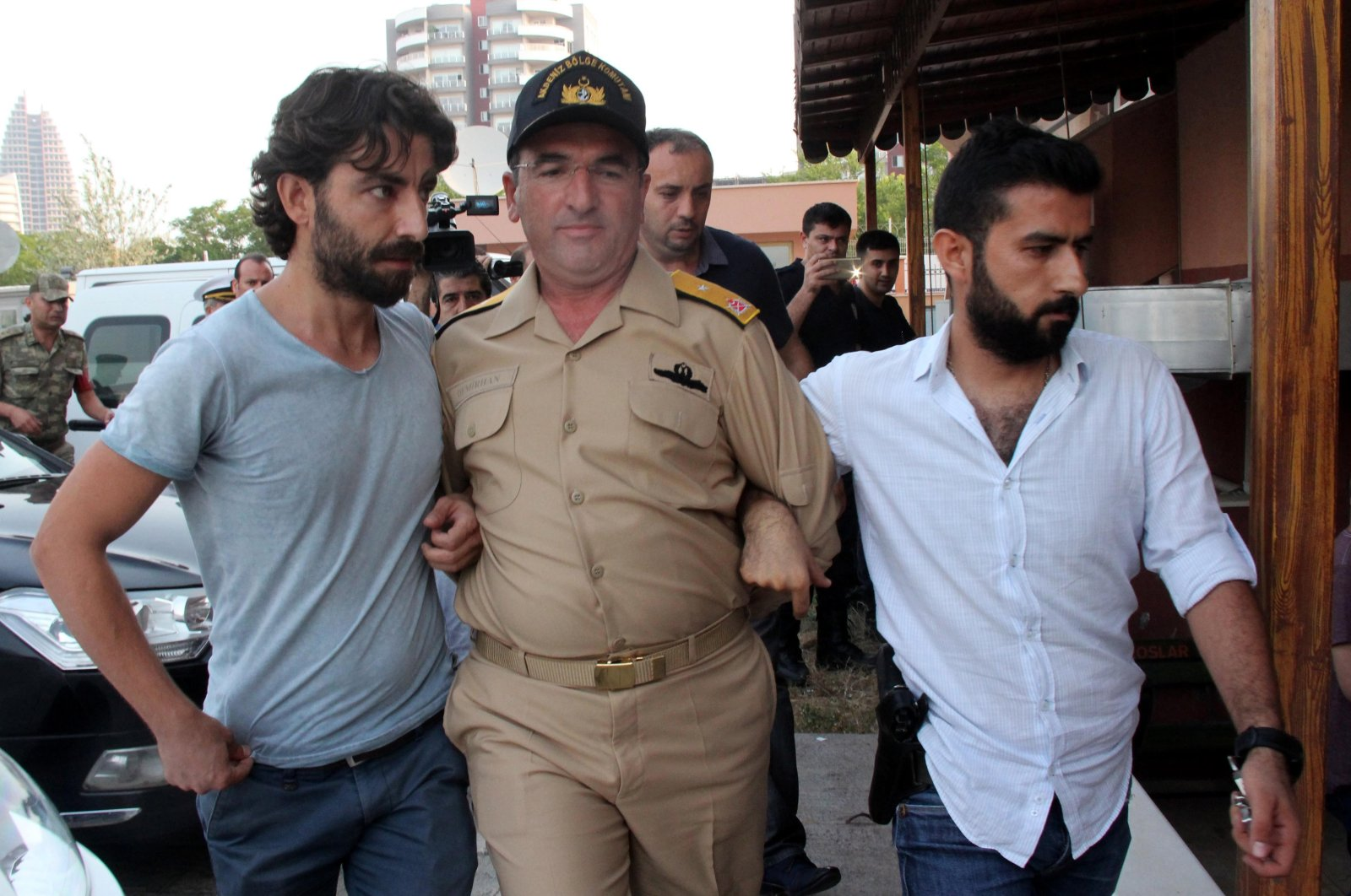 Police officers escort FETÖ member Rear Admiral Nejat Atilla Demirhan after the July 15, 2016 coup attempt, southern Mersin province, Turkey. (IHA Photo)
