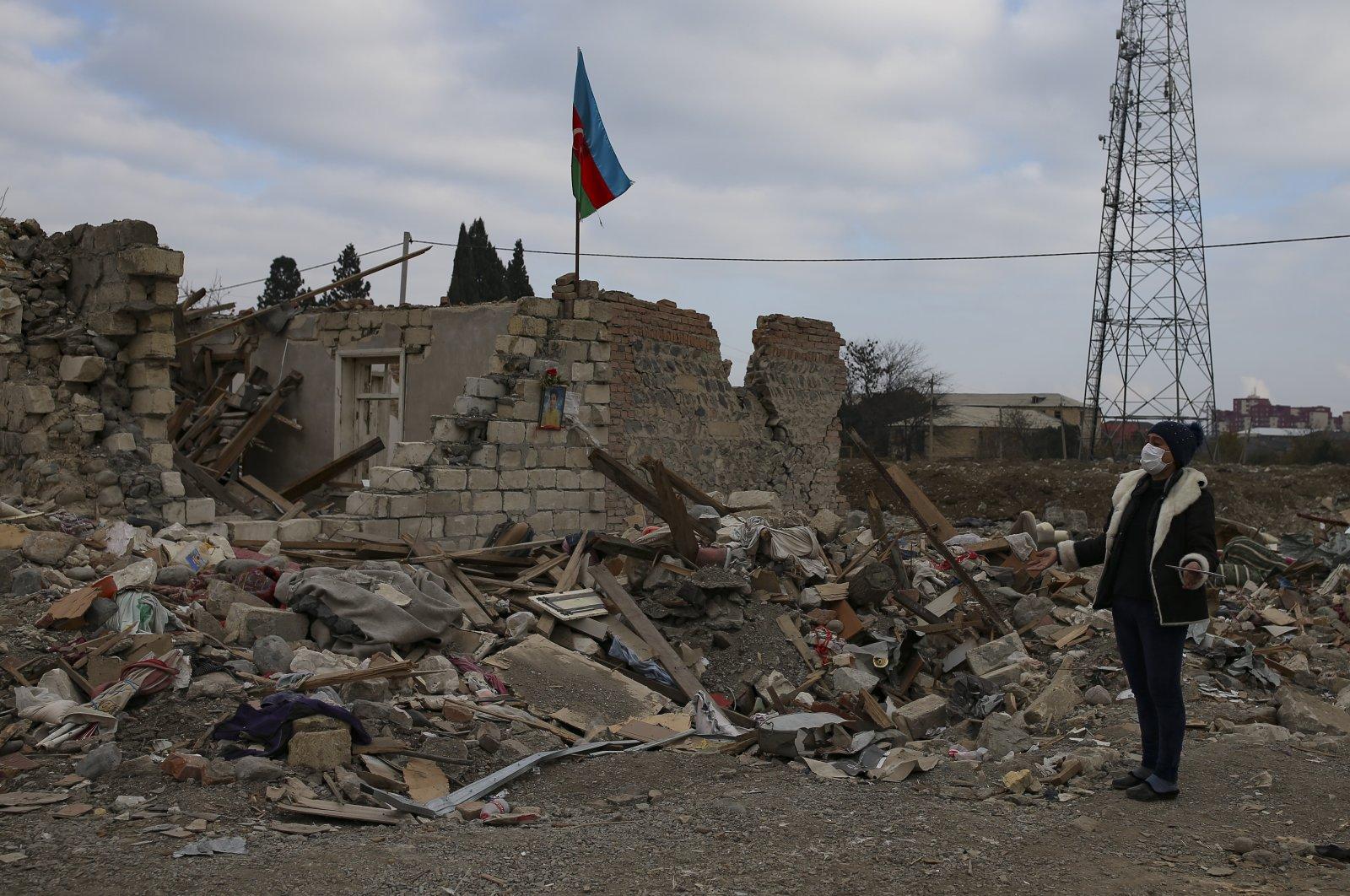 An Azerbaijani man named Saire Guliyeva stands near the ruins of his dwelling, Ganja, Azerbaijan, Nov. 28, 2020. (AP File Photo)