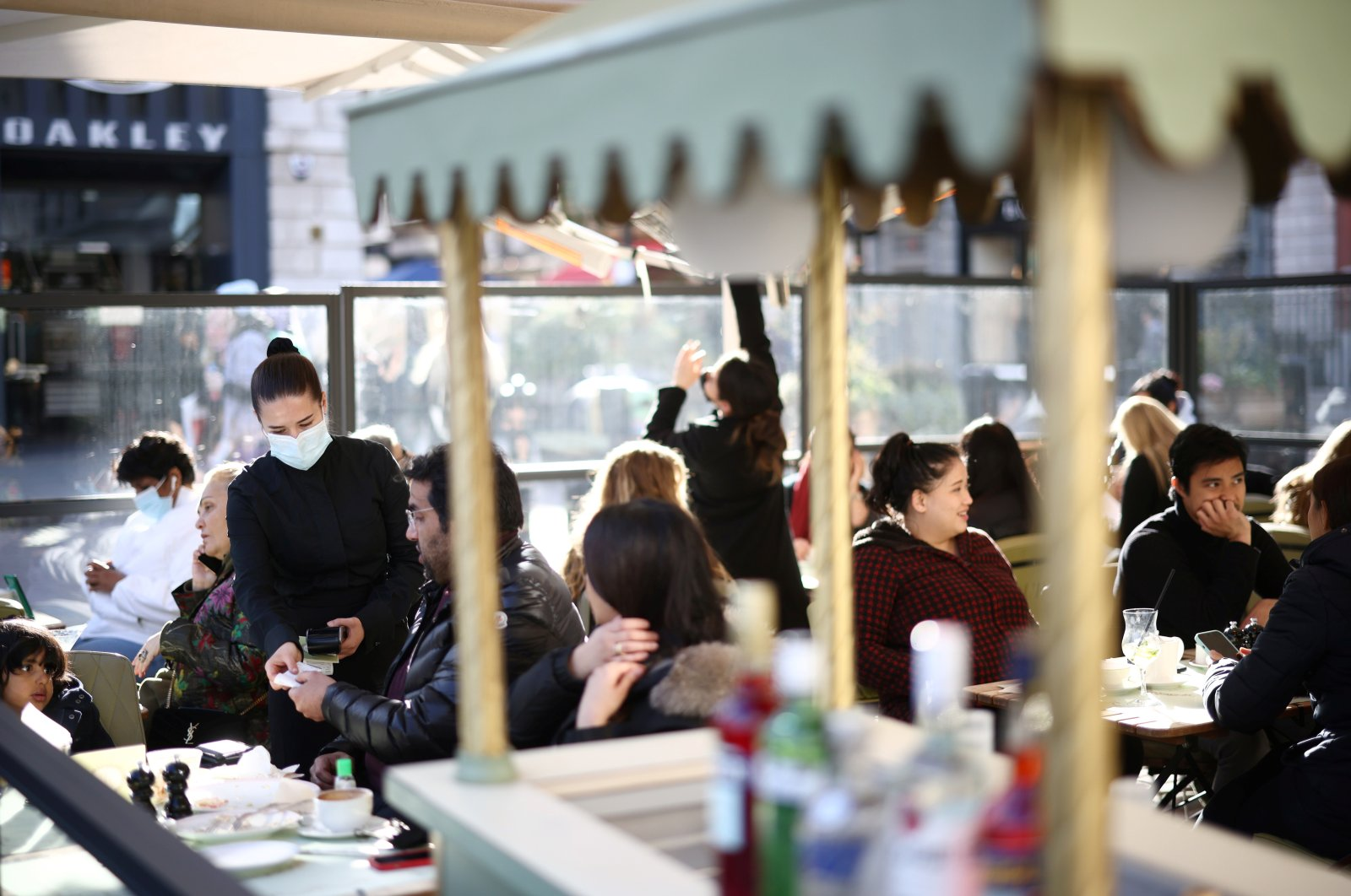 People sit at an outside restaurant area, as the coronavirus restrictions ease, at Covent Garden in London, U.K., April 12, 2021. (Reuters Photo)