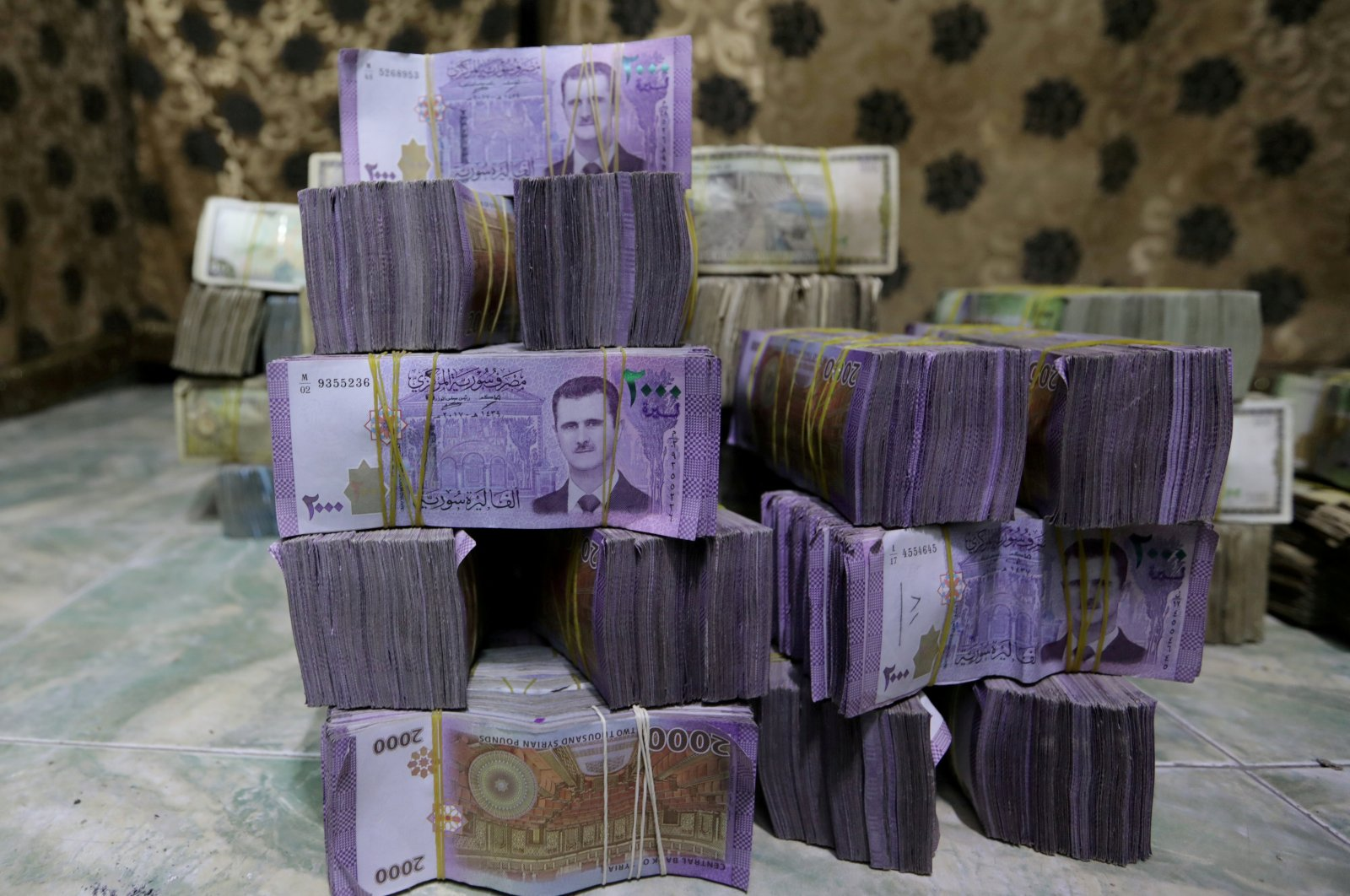 Syrian pounds are stacked inside an exchange currency shop in Azaz, Syria, Feb. 3, 2020. (REUTERS)