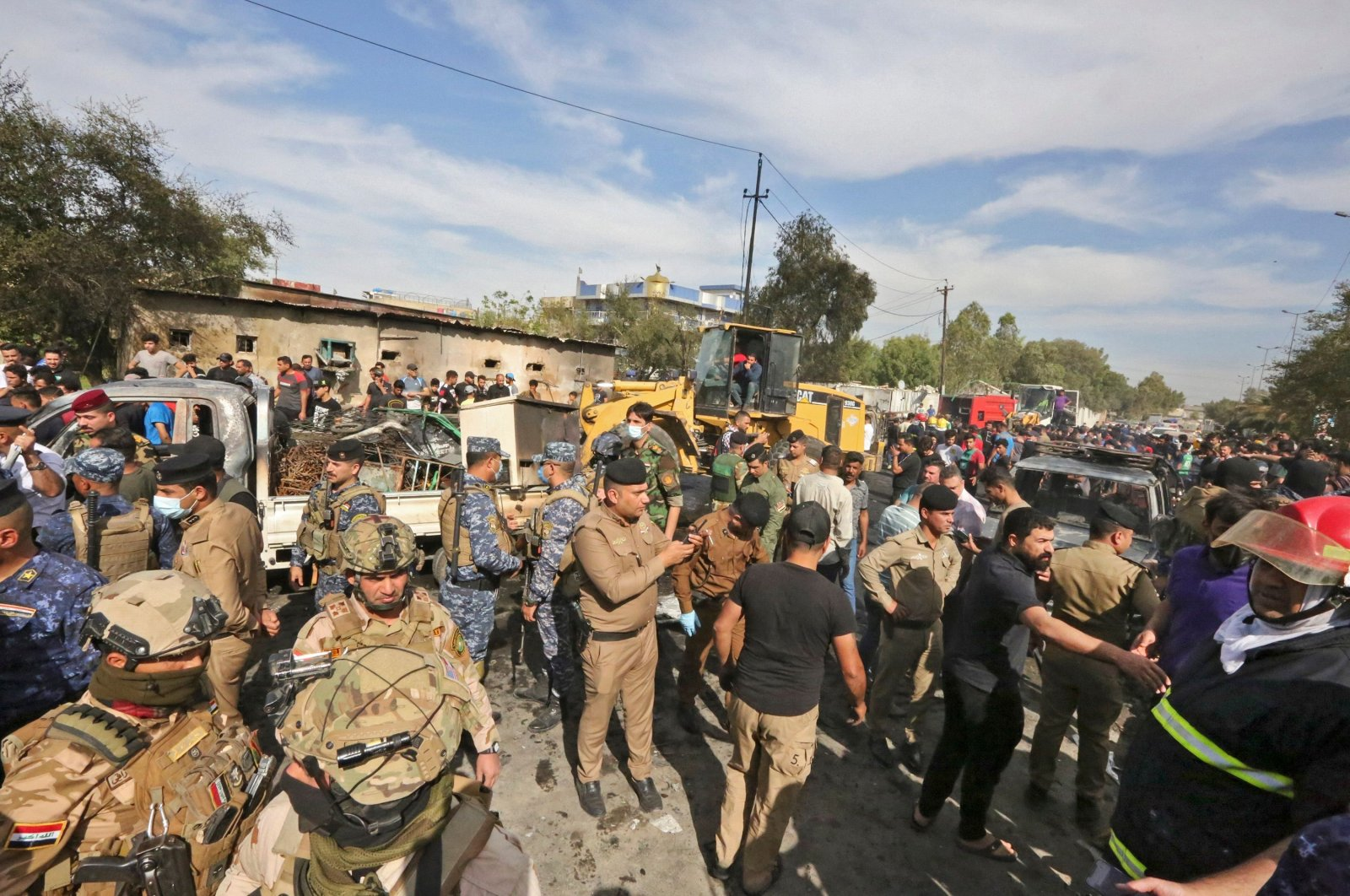 Members of the Iraqi army and security forces gather at the scene of an explosion in the Habibiya district of the Sadr City suburb of Iraq's capital Baghdad, April 15, 2021. (AFP Photo)