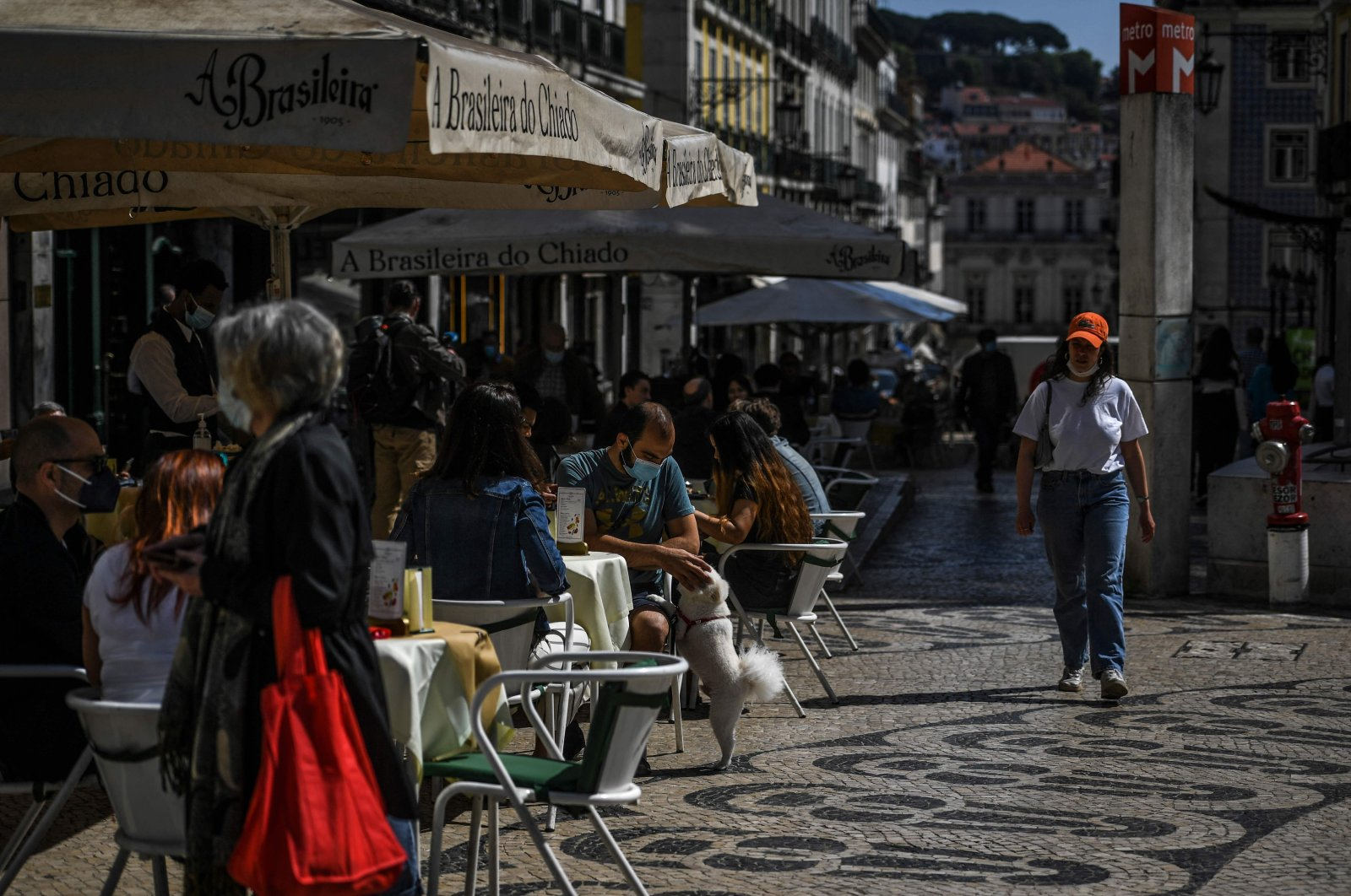 People sit at a cafe terrace after the Portuguese government eased coronavirus restrictions, in the Chiado district of Lisbon, Portugal, April 5, 2021. (AFP)
