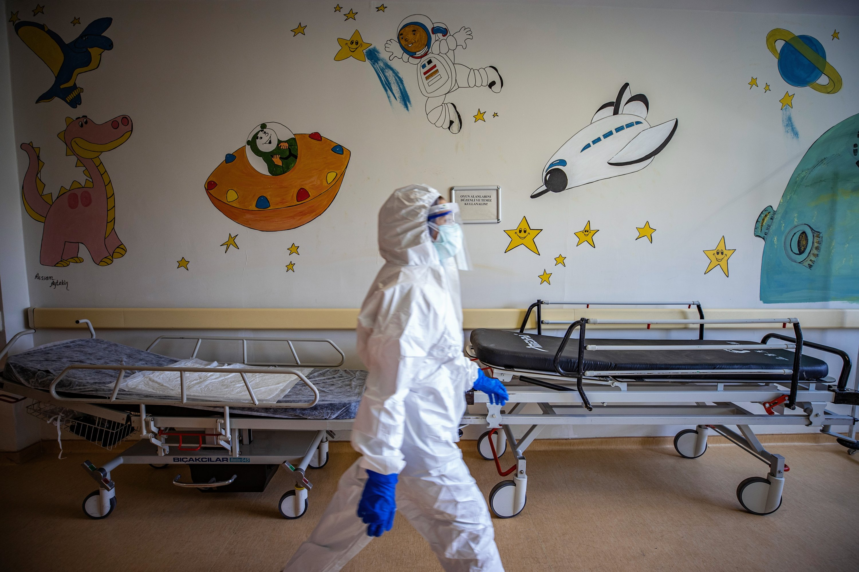 A hospital staff member walks past a wall adorned with drawings at the hospital, in Istanbul, Turkey, April 16, 2021. (AA PHOTO)