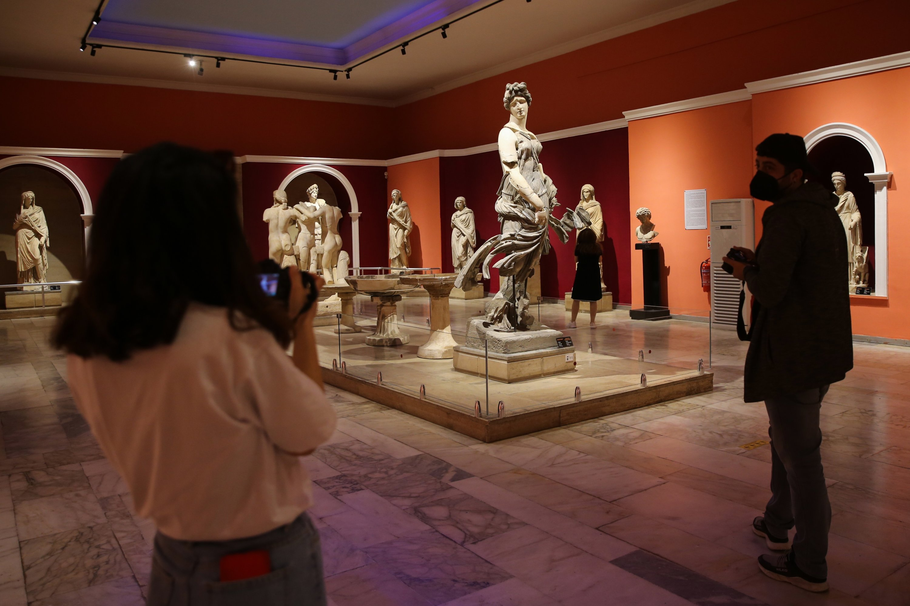 Two visitors take photos of sculptures in the Antalya Museum, Antalya, southern Turkey, April 16, 2021. (AA Photo)
