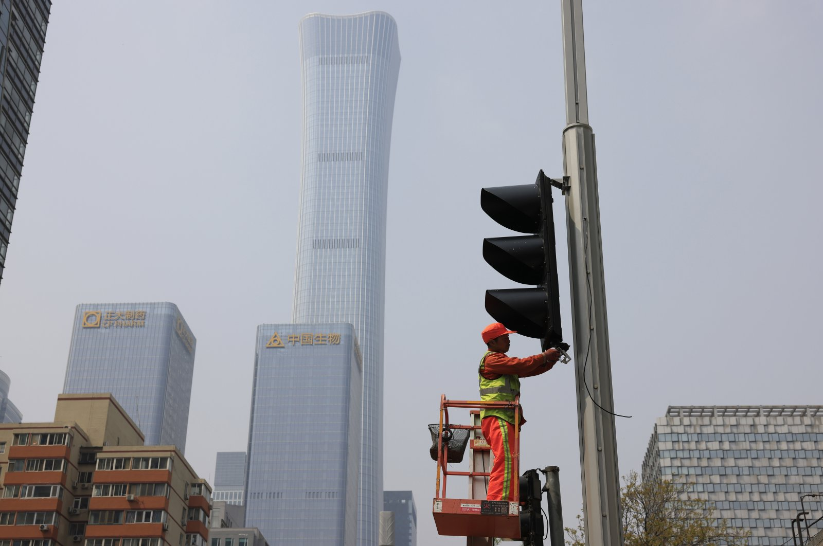 A worker installs new traffic lights at a junction in Beijing on Thursday, April 15, 2021. (AP Photo)