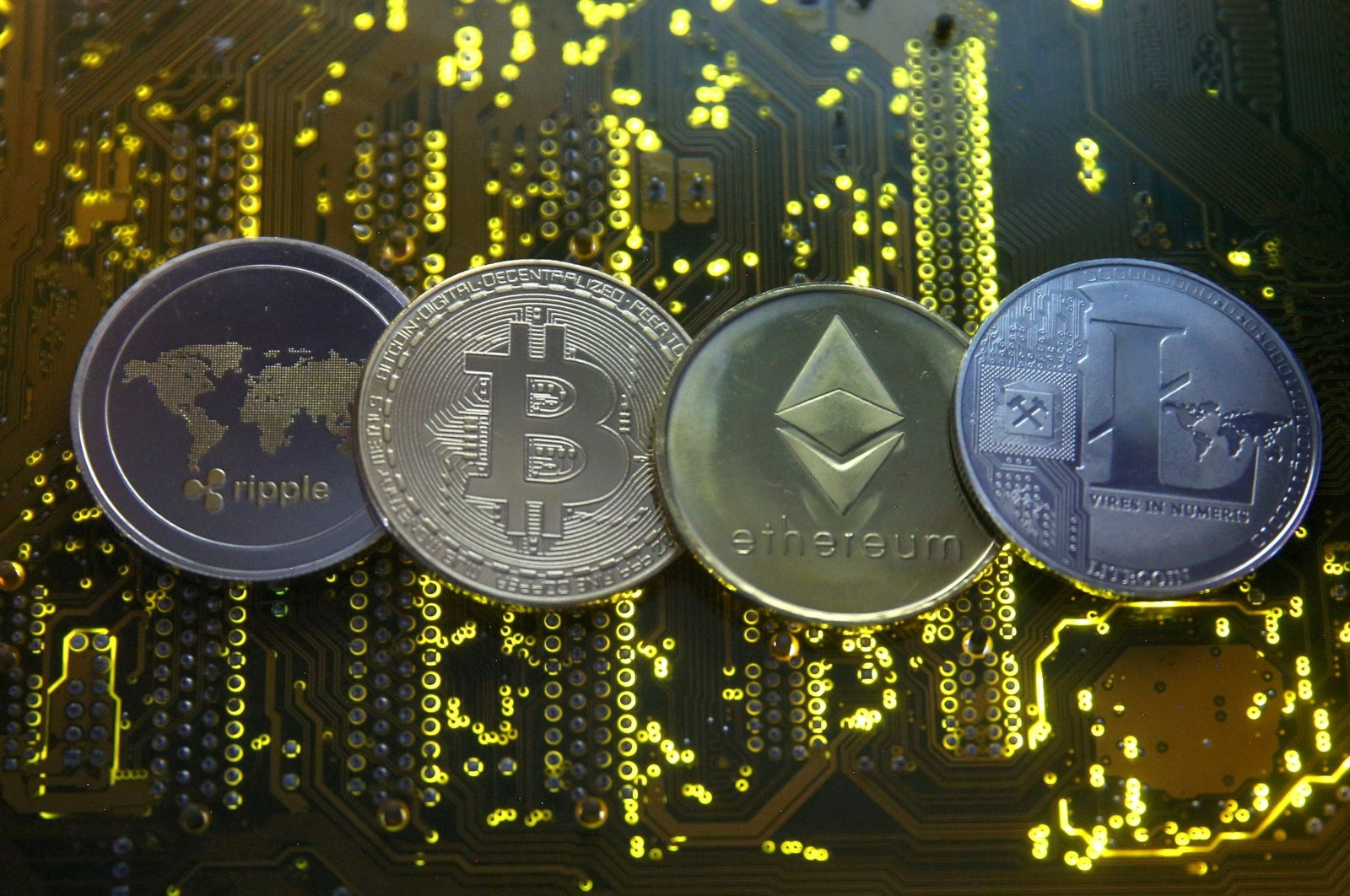 Representations of the Ripple, bitcoin, etherum and Litecoin virtual currencies are seen on a PC motherboard in this illustration, Feb. 14, 2018. (Reuters Photo)