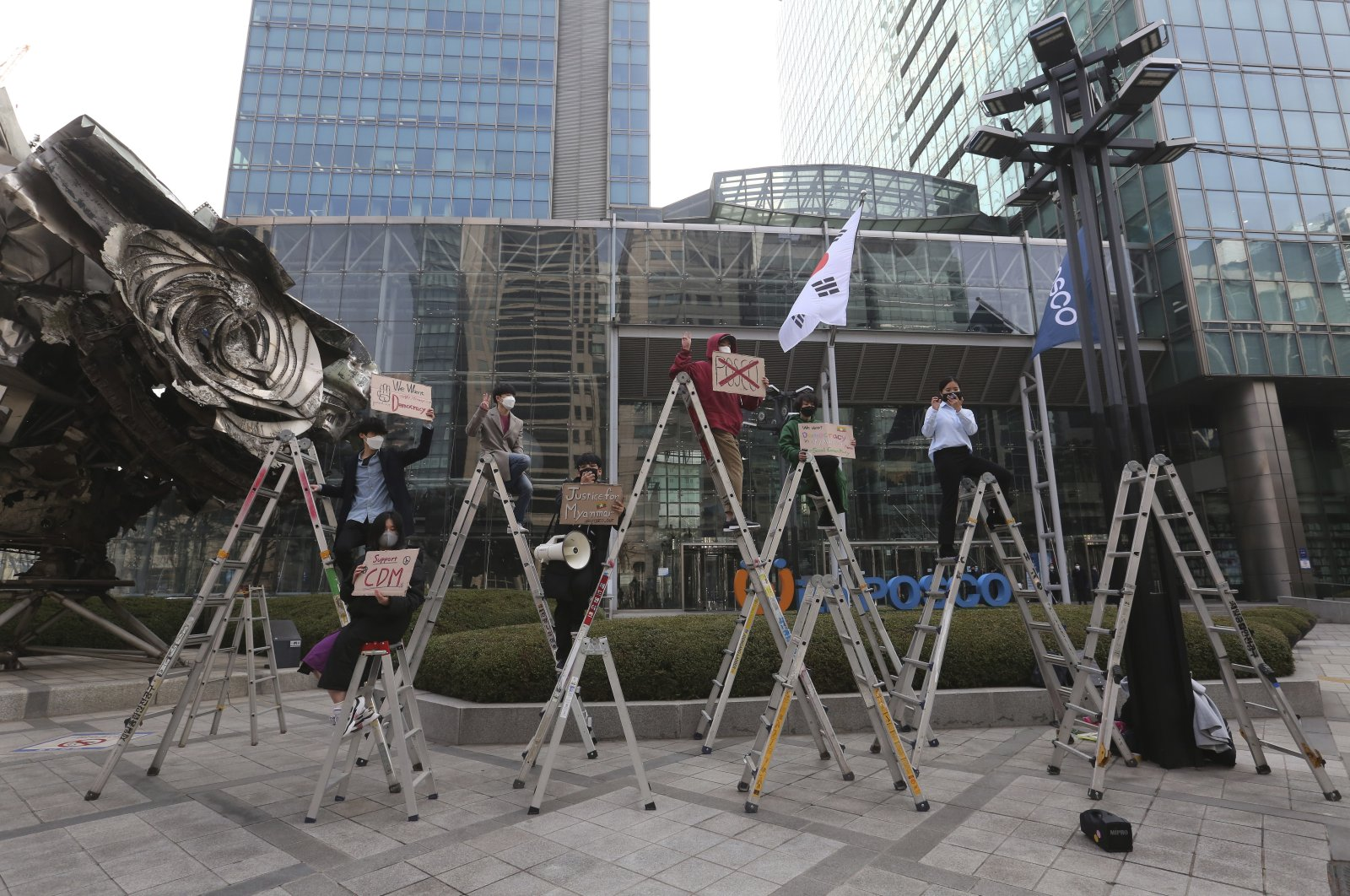 South Korean peace activists on the ladders stage a rally supporting Myanmar's democracy, outside the POSCO office in Seoul, South Korea on Feb. 22, 2021. (AP Photo)