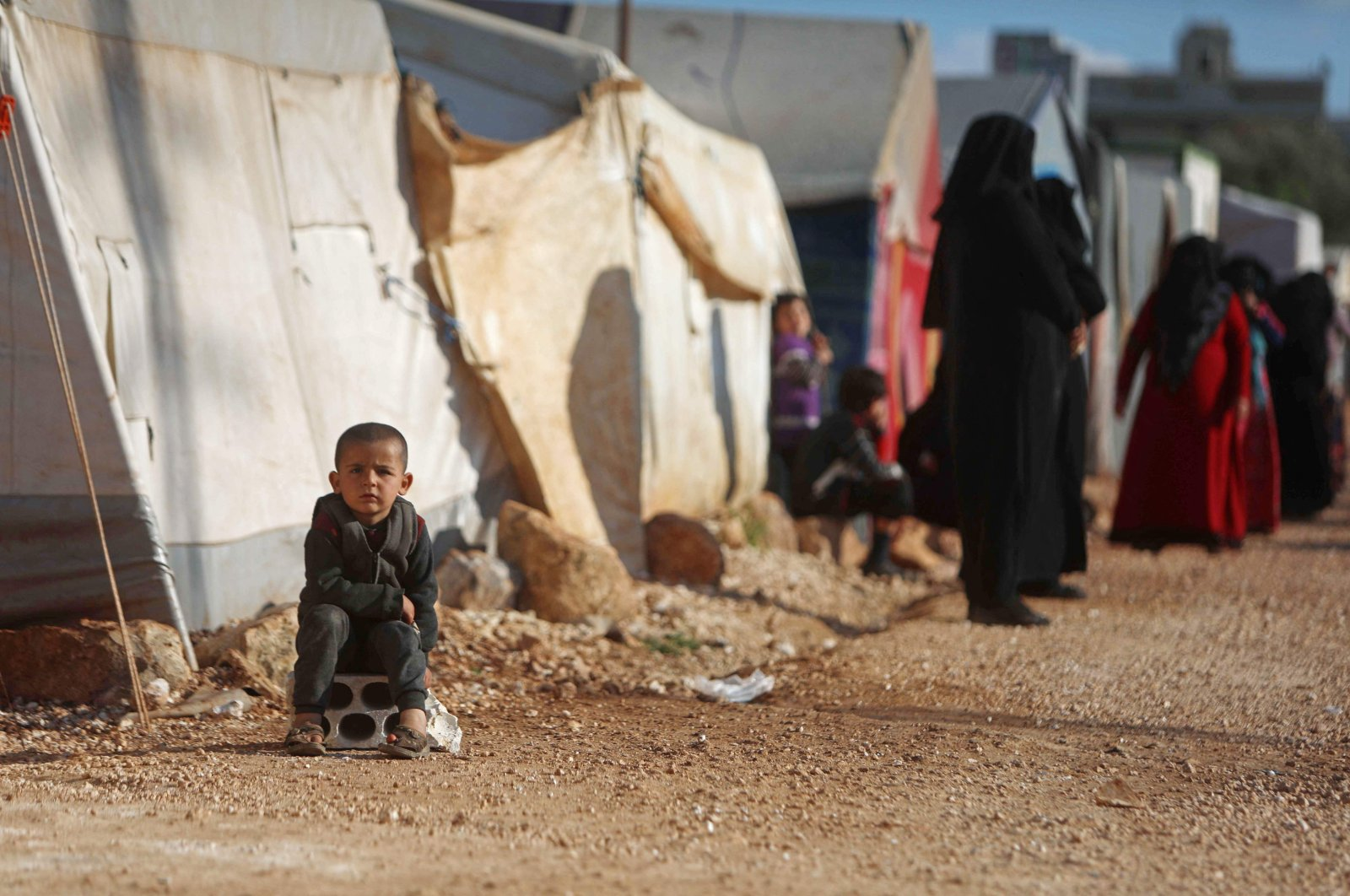 A child sits near displaced Syrians lining up to collect plates of food prepared by a local charity for the Ramadan fast-breaking meal at a camp for people displaced by conflict in the town of Sarmada in Syria's northwestern Idlib province, April 13, 2021. (AFP Photo)