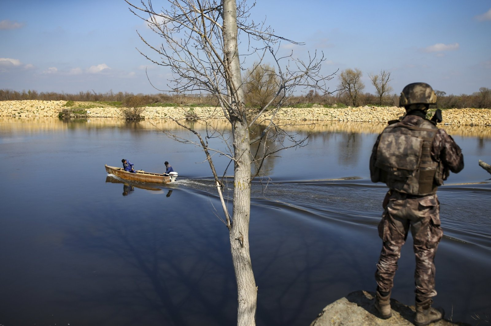 Fishermen sail along the Maritsa river as a Turkish special forces team patrols at the Turkish-Greek border near Karpuzlu village, in Edirne province, northwestern Turkey, March 11, 2020. (AP File Photo)