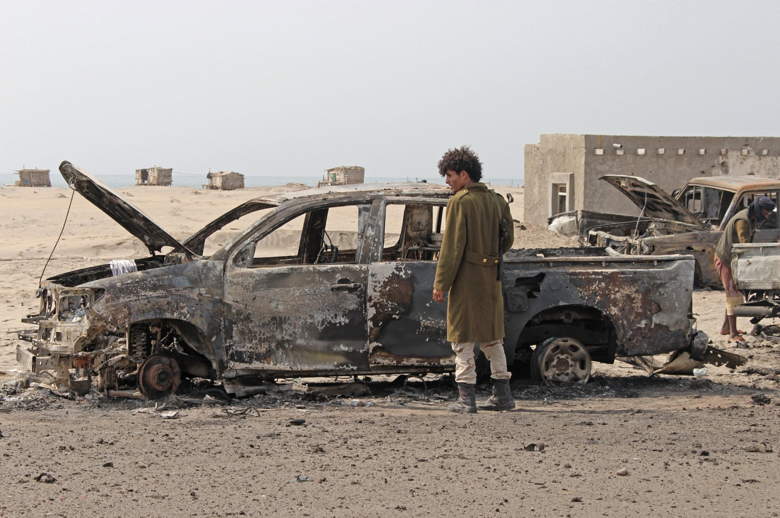 A Yemeni southern separatist fighter inspects the wreckage of government forces vehicles destroyed by UAE airstrikes near Aden, Yemen, Aug. 30, 2019. (AP Photo)