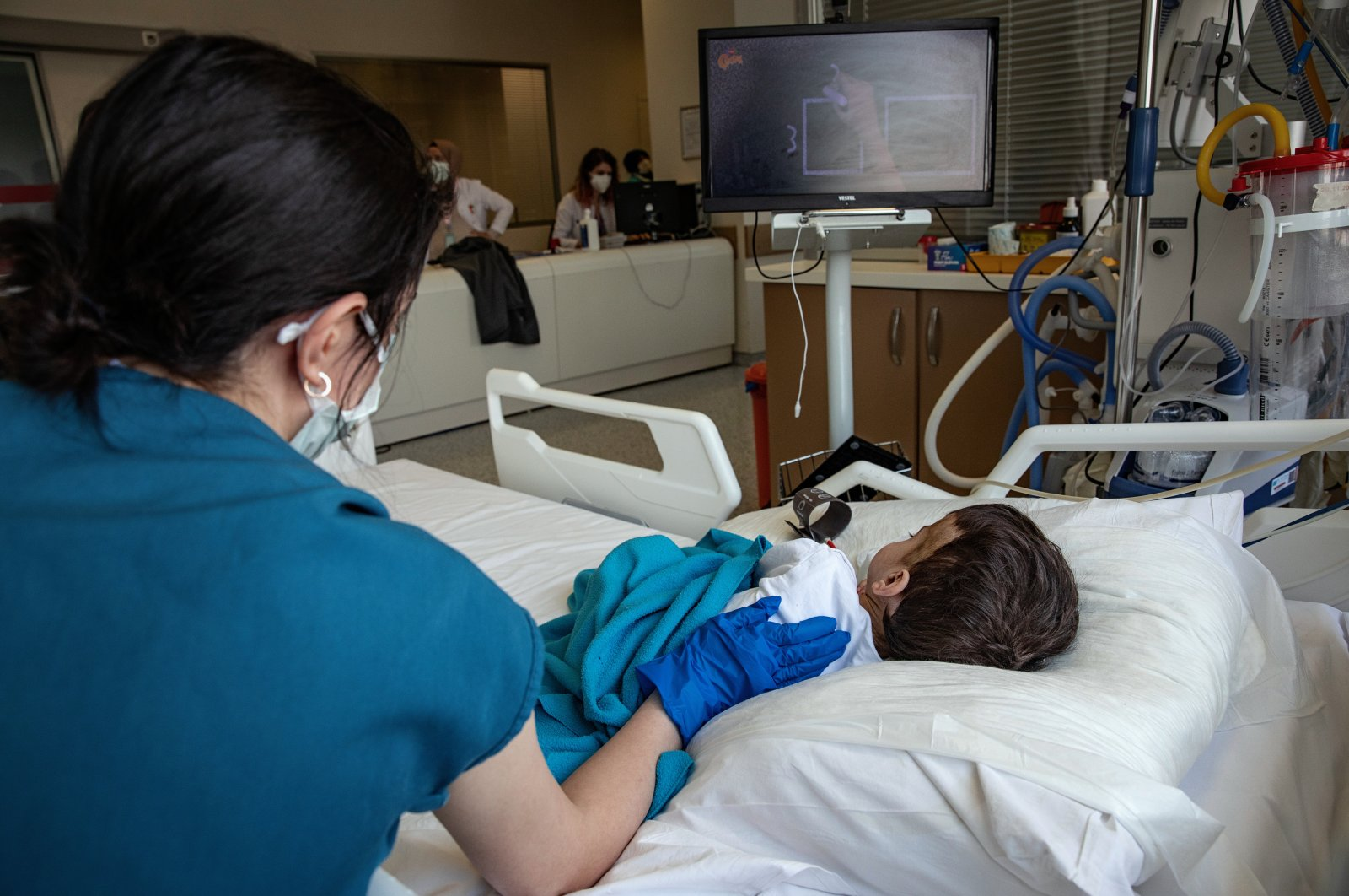 A nurse cares for a young patient watching TV at the hospital, in Istanbul, Turkey, April 16, 2021. (AA PHOTO)