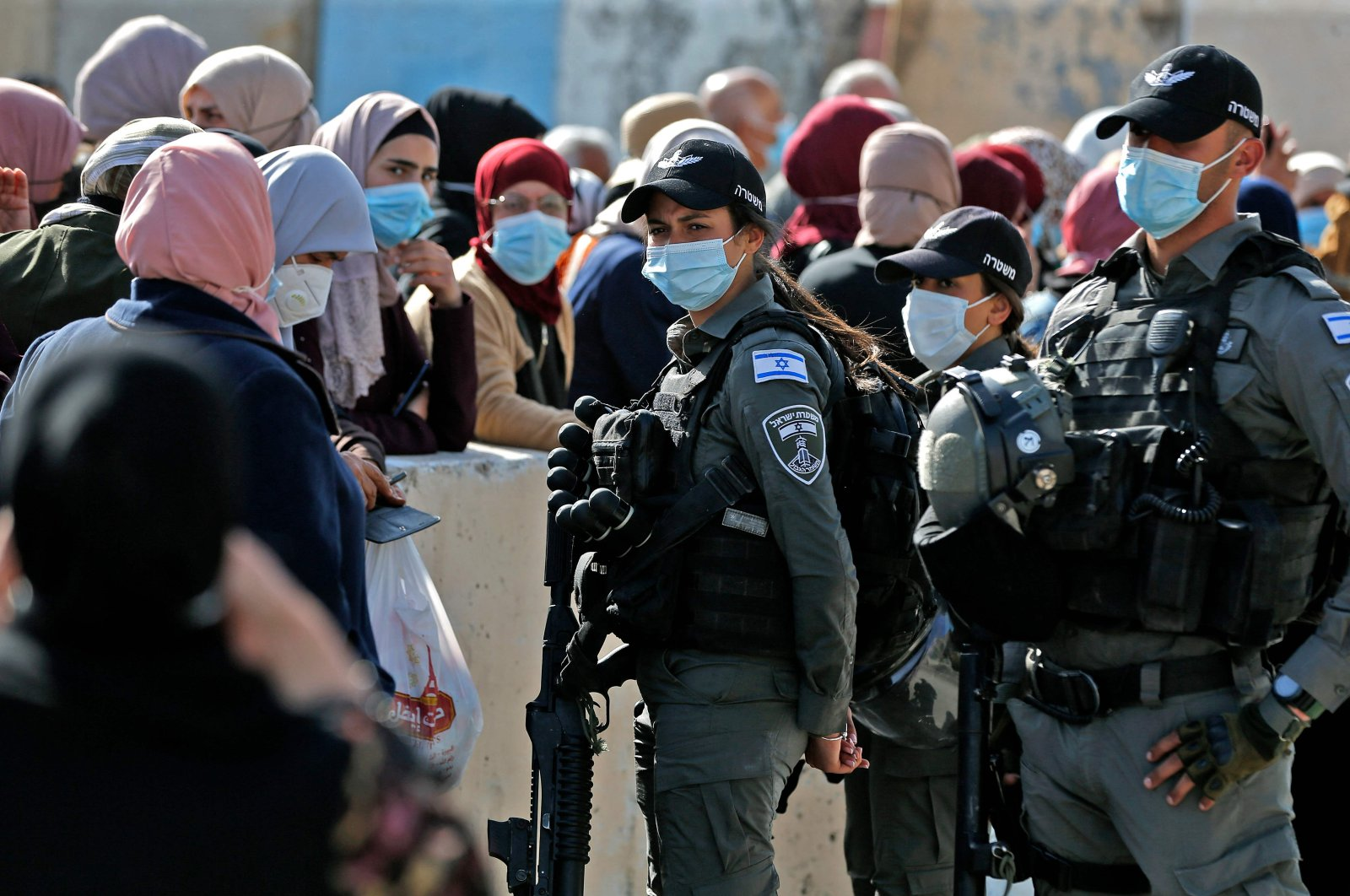 Members of the Israeli security forces man the Qalandia checkpoint near the West Bank town of Ramallah, as Palestinian women wait to enter Jerusalem to attend the first Friday prayers of the Muslim fasting month of Ramadan at the Al-Aqsa Mosque, on April 16, 2021. (AFP Photo)