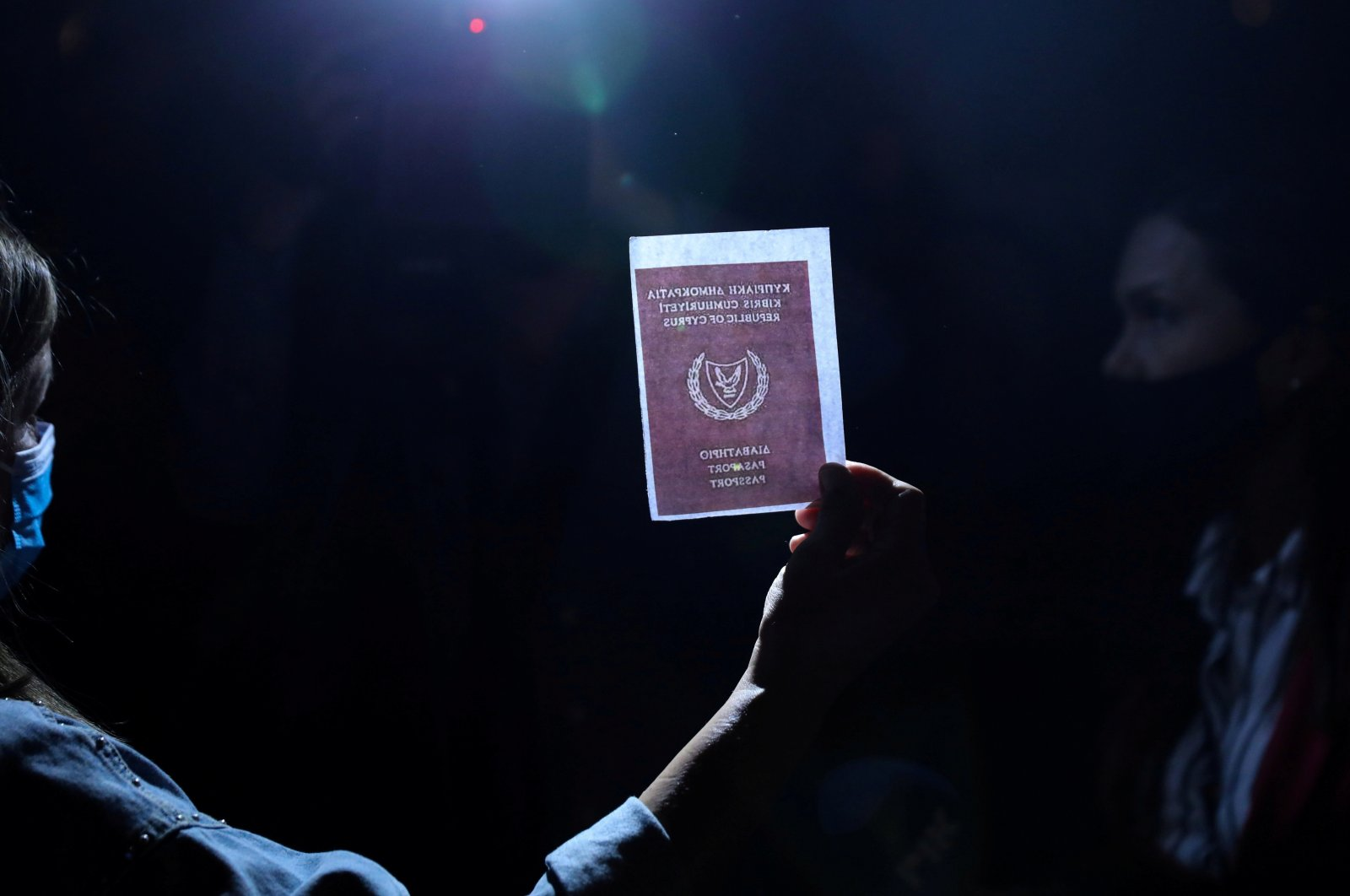 A person holds an image of a passport during a protest against corruption outside the Filoxenia Conference Center, currently hosting Cyprus parliament, in Nicosia, Cyprus Oct. 14, 2020. (Reuters Photo)