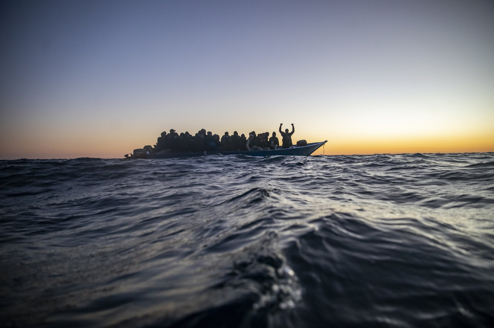 Migrants and refugees from different African nationalities wait for assistance aboard an overcrowded wooden boat, as aid workers of the Spanish NGO Open Arms approach them in the Mediterranean Sea, international waters, at 122 miles off the Libyan coast, Feb. 12, 2021. (AP Photo)