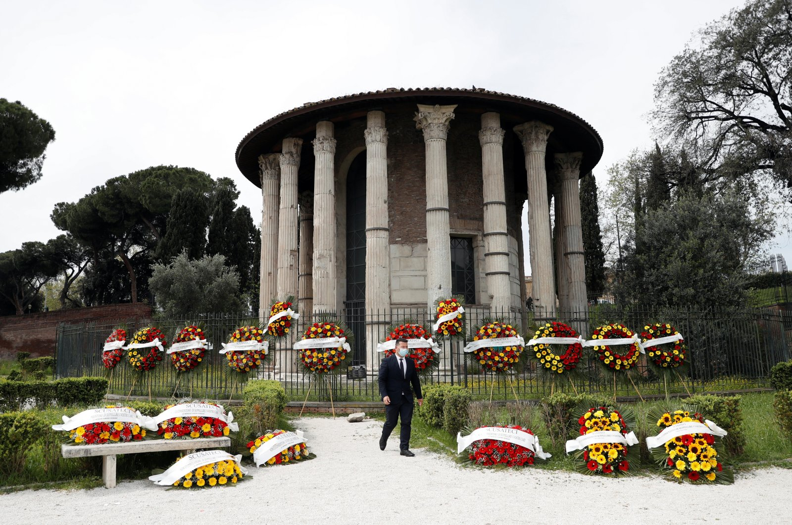 """A man walks past funeral wreaths with the words """"Sorry, but they don't allow us to bury your loved ones"""" written across them laid out by funeral workers in Rome, Italy, April 16, 2021. (Reuters Photo)"""