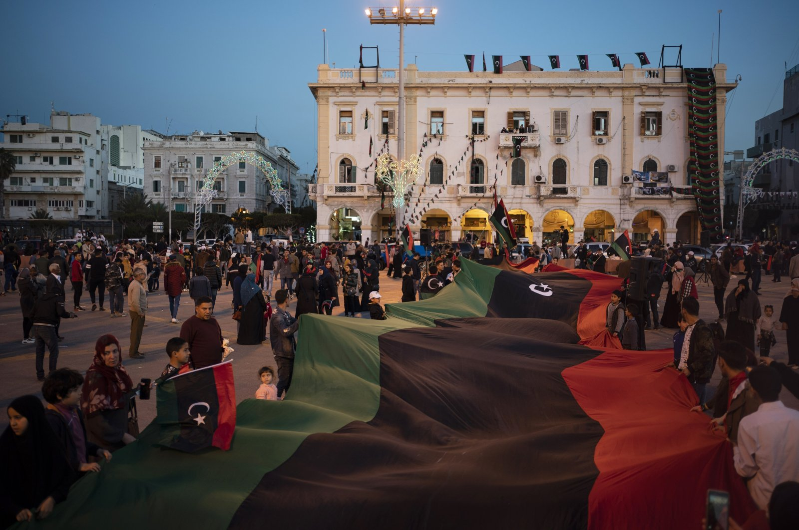 People carry a giant Libyan flag at the Martyrs square during a march commemorating the anniversary of anti-Gadhafi protests in Tripoli, Libya, Feb. 25, 2020. (AP Photo)