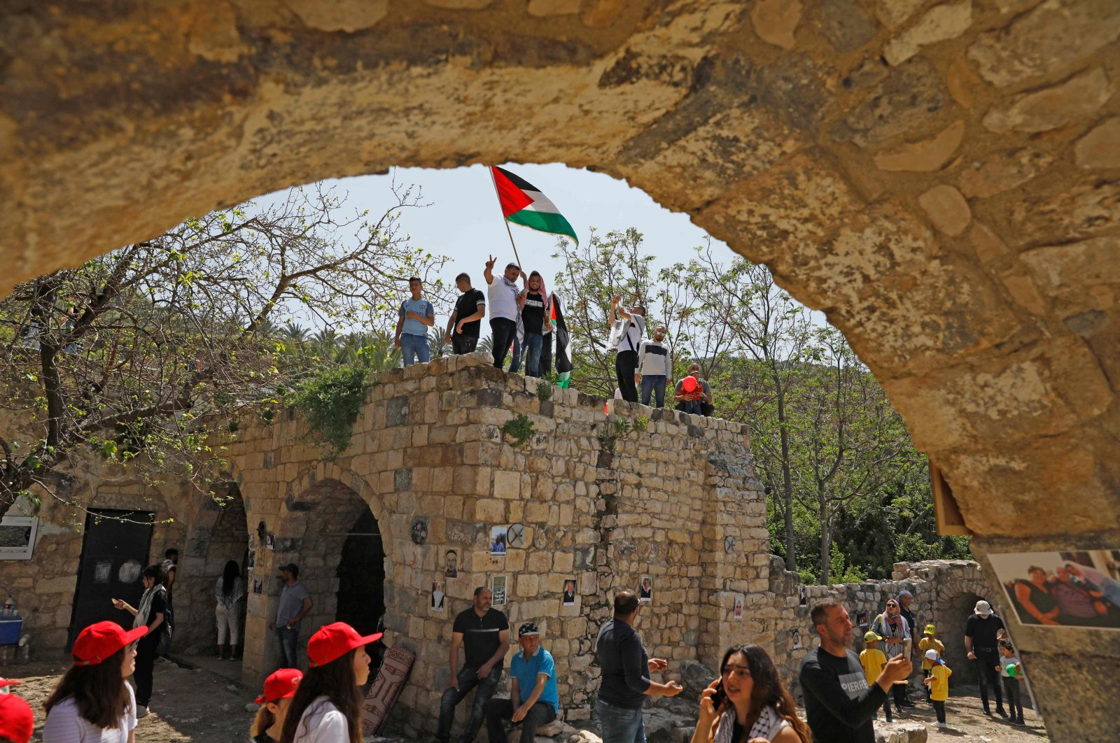 As Israelis mark Independence Day, celebrating the 73th year since the founding of the Jewish State, Arab Israelis wave Palestinian flags in the abandoned Arab village of Kfar Hattin to call for the right of return for Palestinian refugees who fled their homes or were expelled during the 1948 war that followed the creation of Israel, near Tiberias, northern Israel, April 15, 2021. (AFP Photo)