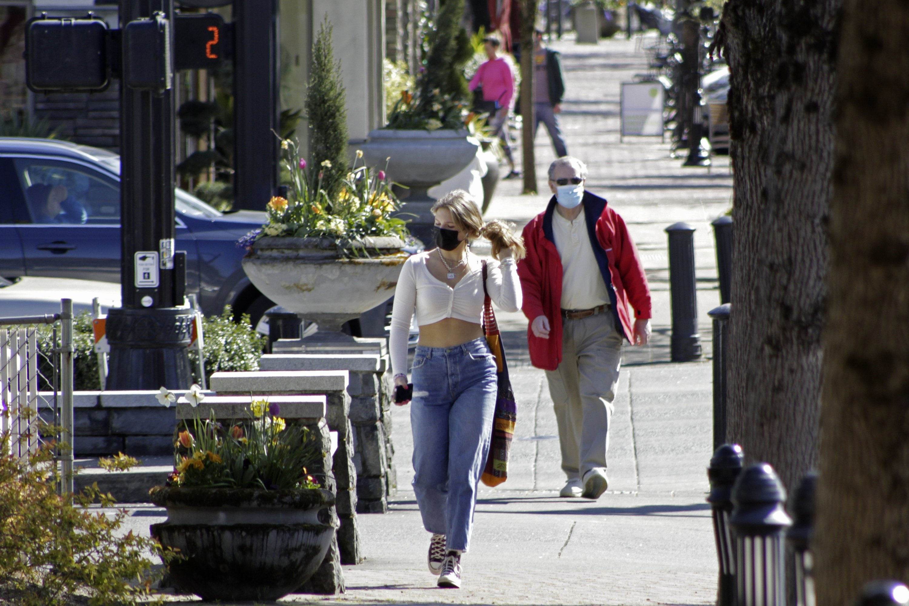 Residents wearing masks walk in downtown Lake Oswego, Oregon, the U.S., April 11, 2021. (AP Photo)