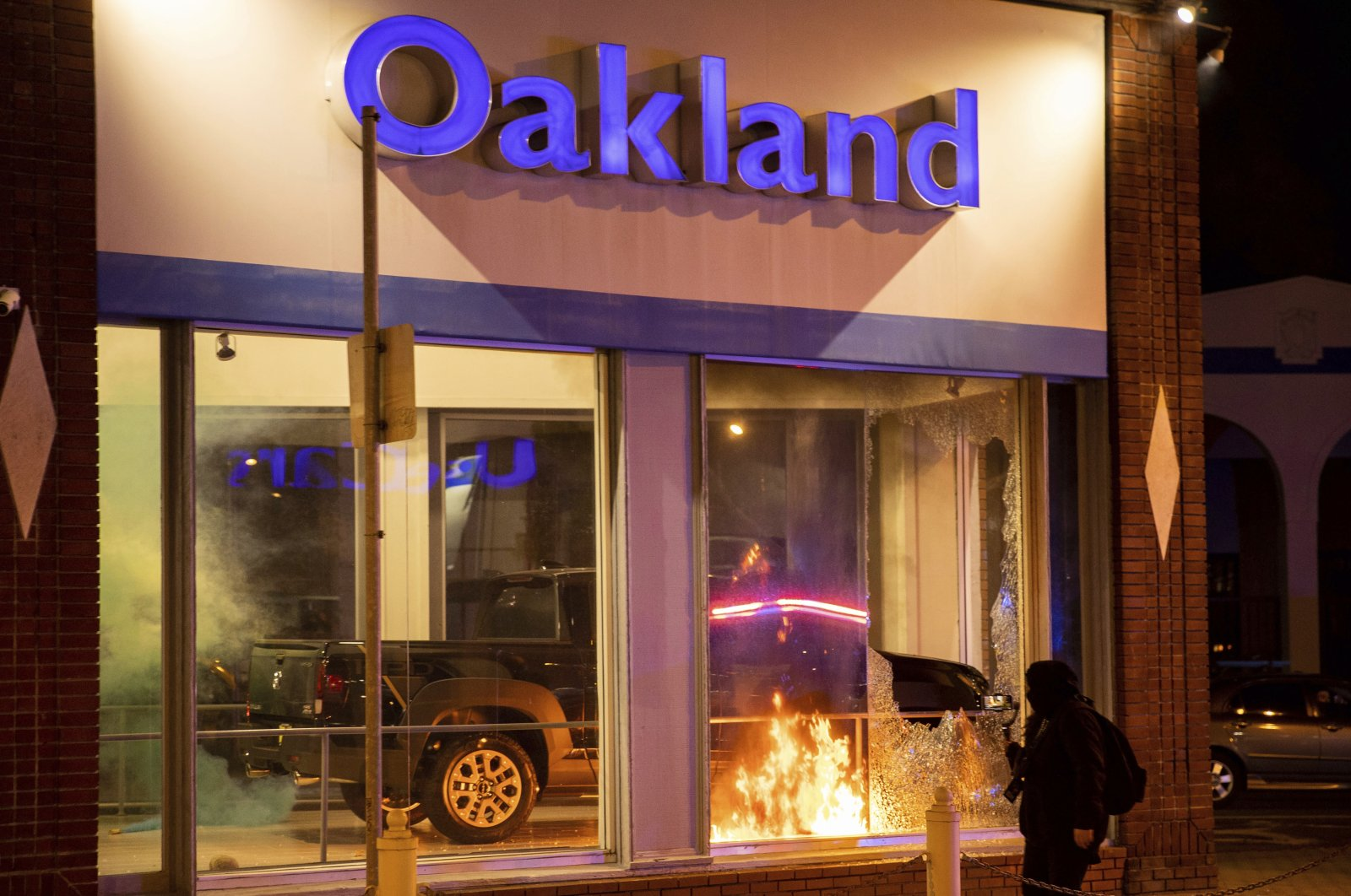 Demonstrators set fires at a Honda dealership during a protest against police brutality in Oakland, California, U.S., April 16, 2021. (AP Photo)