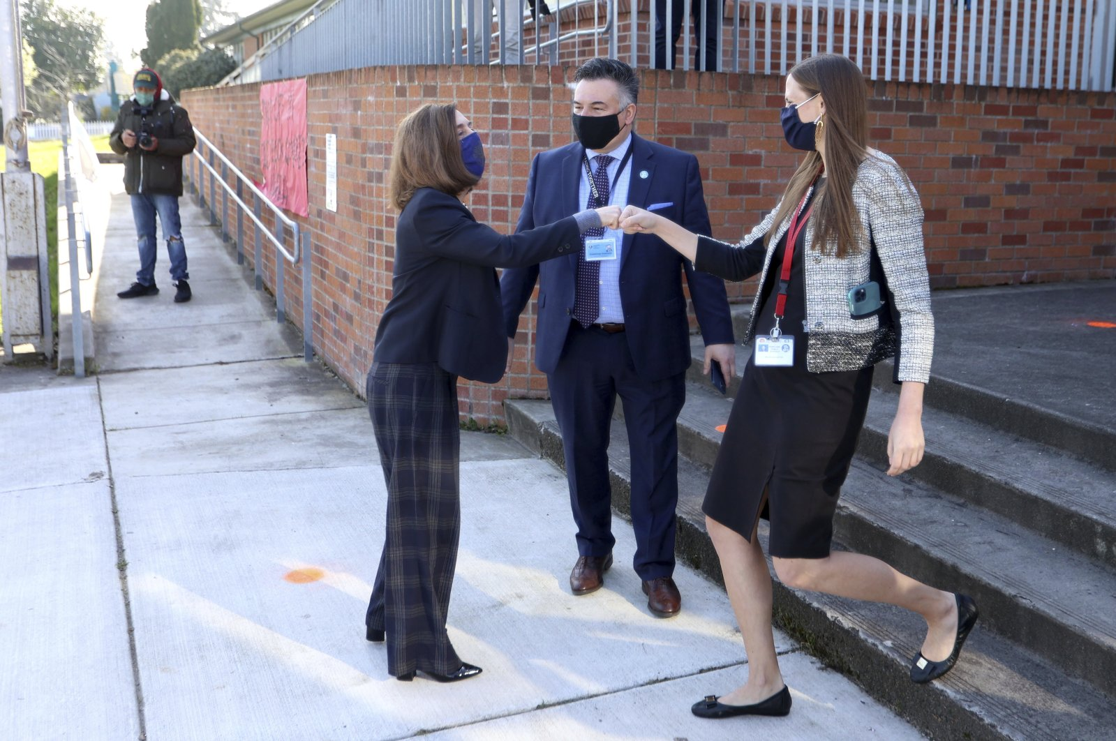 Oregon Governor Kate Brown (L) fist bumps in front of Portland Public Schools Superintendent Guadalupe Guerrero (C) with Scott Elementary School principal Megan McCarter (R) and on the first day of hybrid instruction at Scott Elementary School, Portland, Oregon, the U.S., April 1, 2021. (AP Photo)