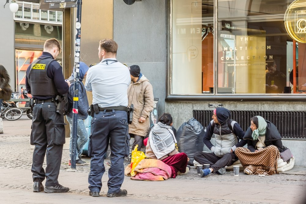 Two police officers look at the paperwork of immigrants who are sitting on the street, Copenhagen, Denmark, April 6, 2017. (Shutterstock Photo)